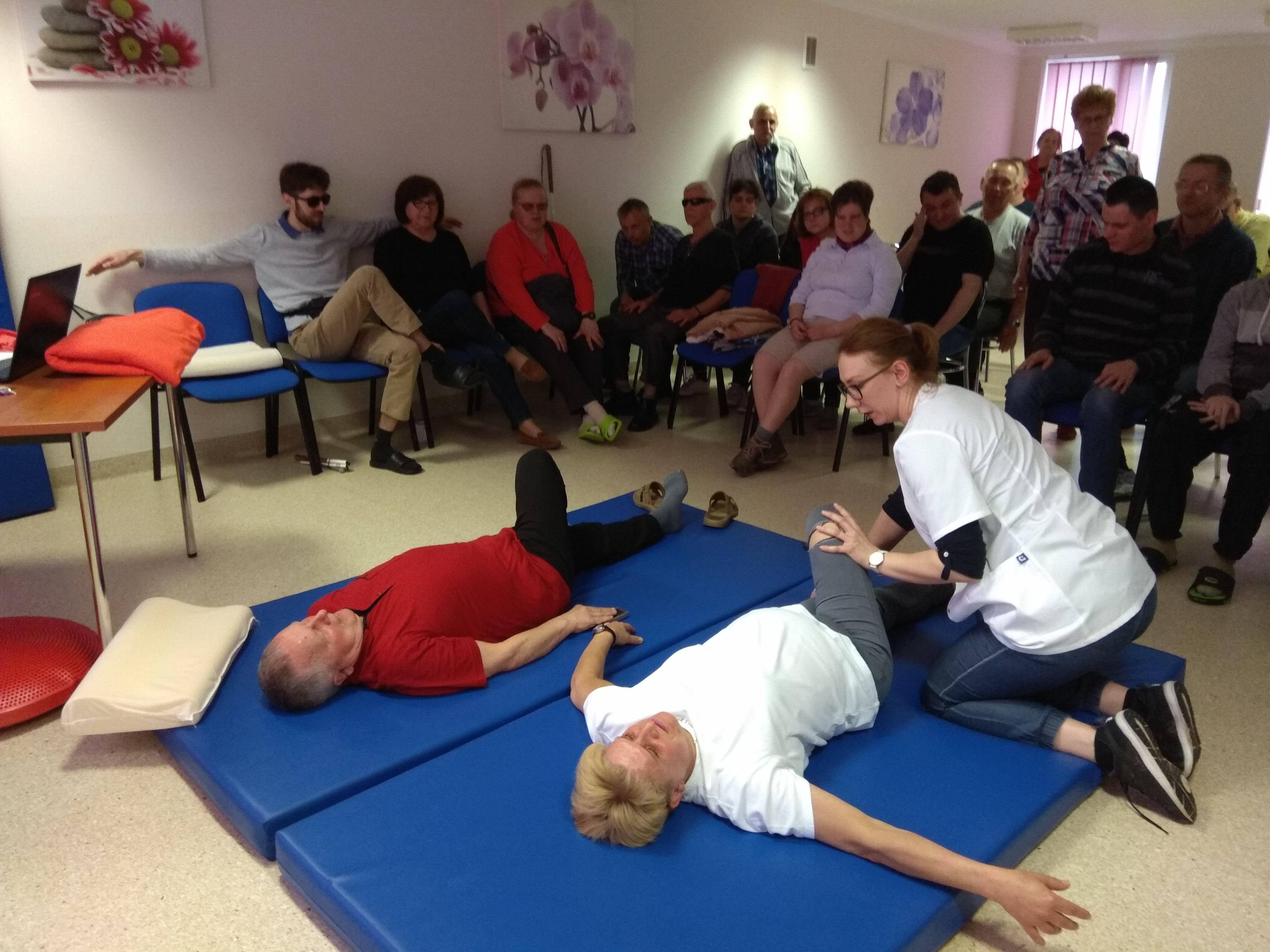 Podczas prezentacji ćwiczenia. Na dwóch niebieskich materacach leżą krótkowłosa blondynka w białym podkoszulku i mężczyzna w czerwonym T-shircie. Leżąc na plecach, lewą nogę trzymają wyprostowaną na materacu, a prawą kończynę zgiętą w kolanie pochylają na lewą stronę. Pani rehabilitantka pomaga pochylić kobiecie kończynę we właściwy sposób. Na krzesłach siedzą przyglądający się ćwiczeniu pozostali zjazdowicze.