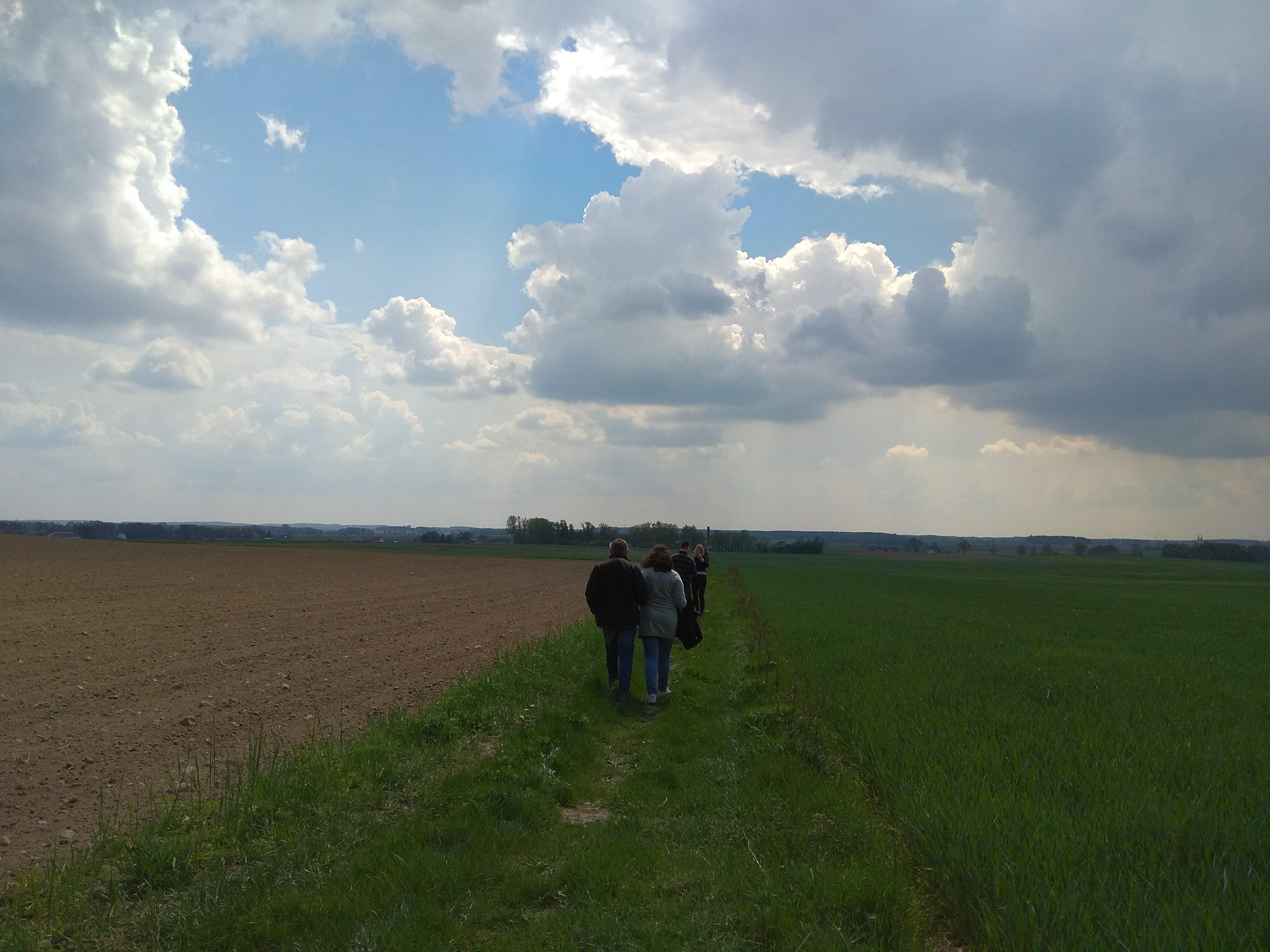 Pejzaż otwartej przestrzeni. Z lewej strony ziemia, prawa strona porośnięta trawą, nad nimi błękitne niebo z kłębiastymi chmurami. Po środku zdjęcia, oddalające się sylwetki ludzi.
