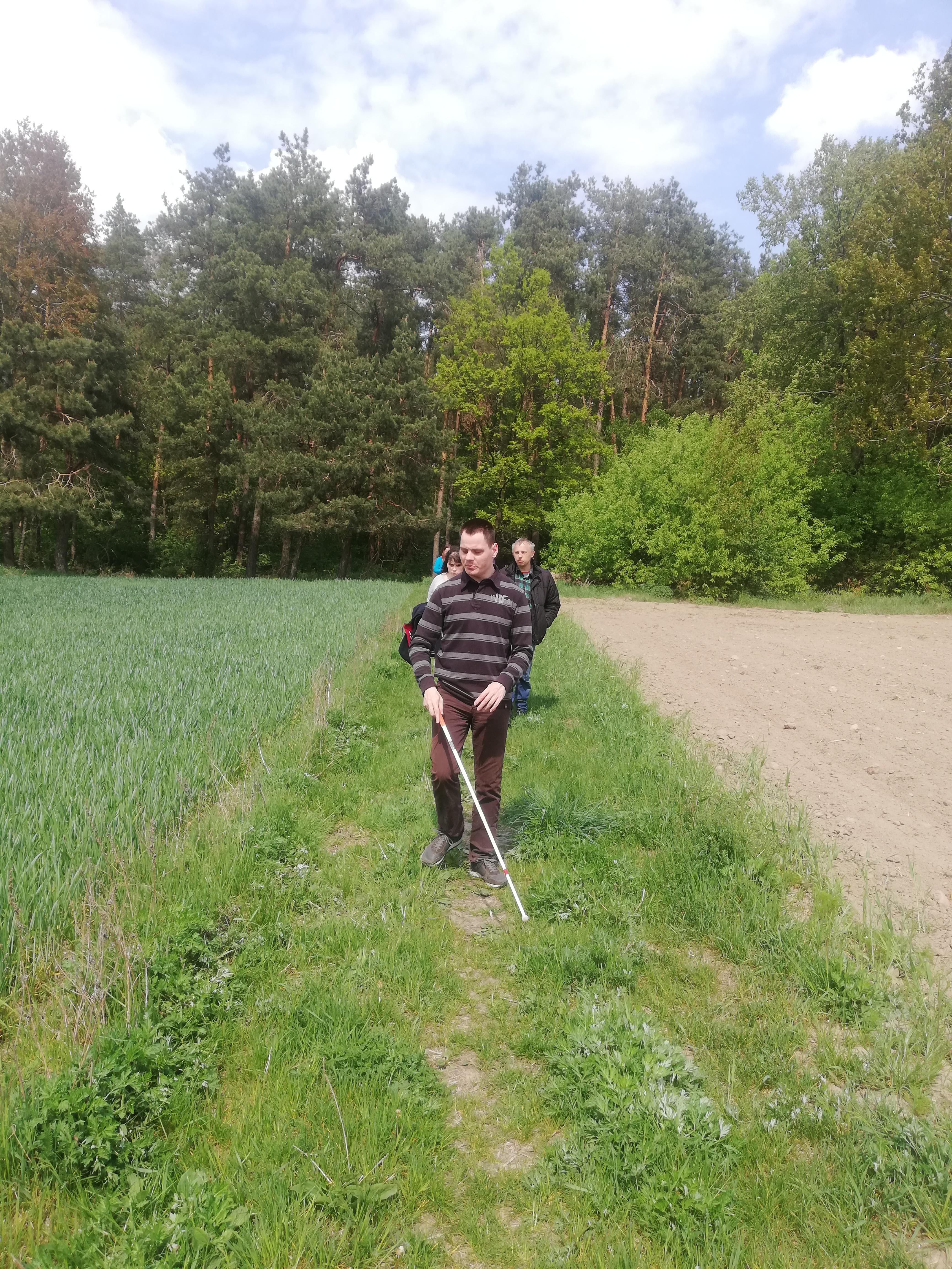 Kilka osób idących gęsiego po zielonej trawie. Szyk otwiera brunet idący z laską. Ubrany jest w bluzę w czarno-szare pasy. Na ostatnim planie pas liściastych drzew.