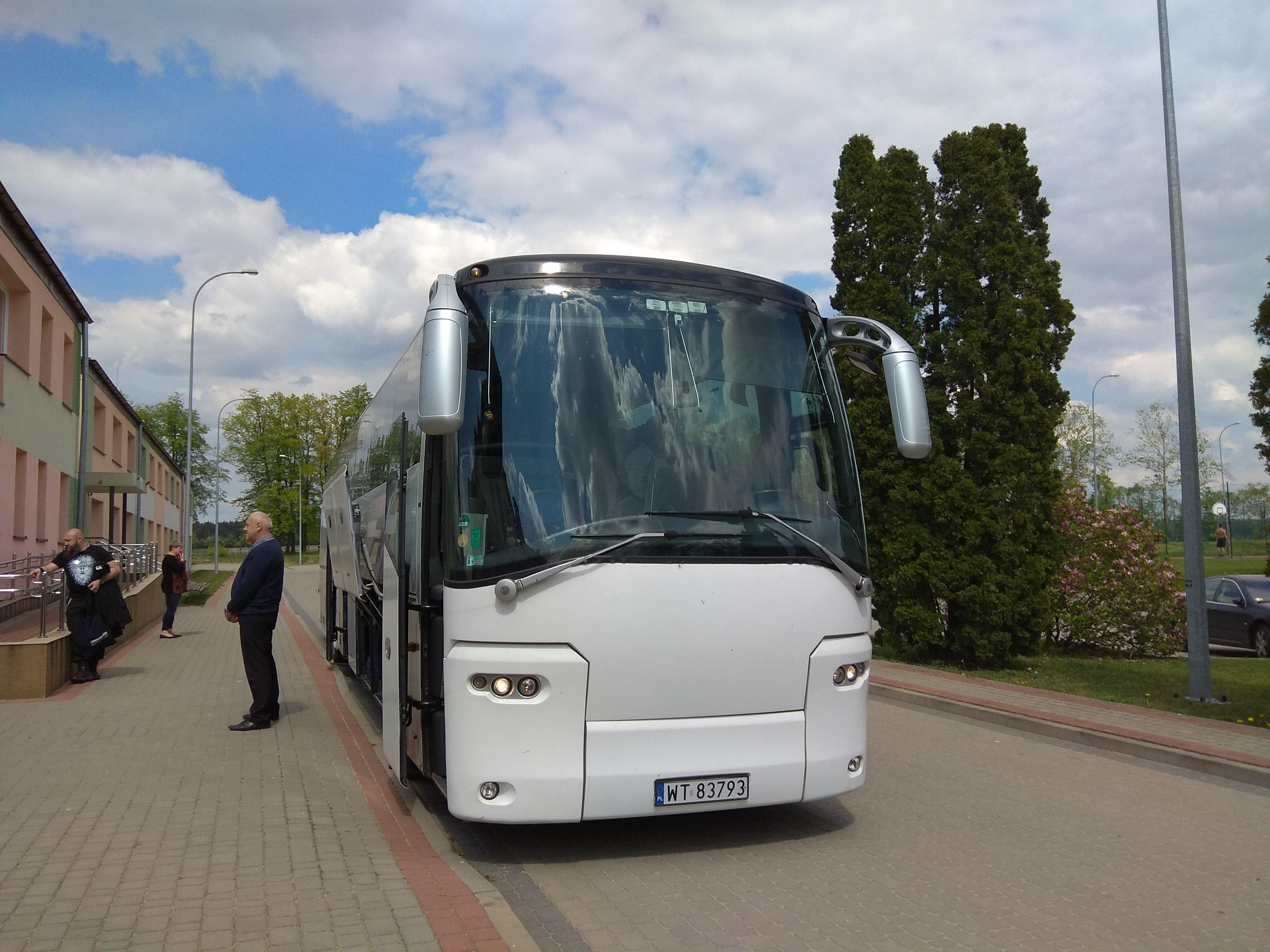 Kierowca w oczekiwaniu na gości ośrodka stojący obok dużego, białego autokaru.
