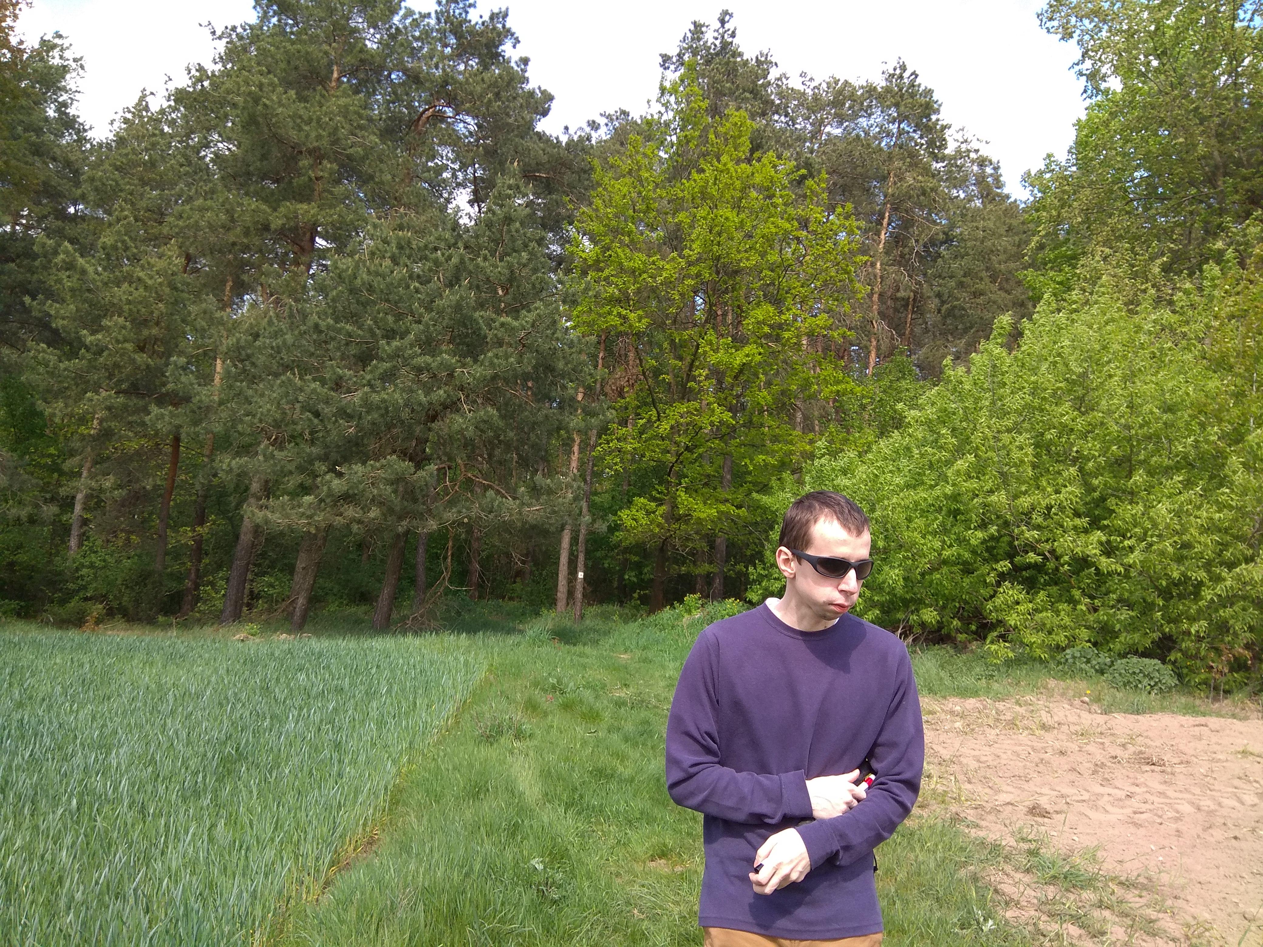 Młody brunet, w przyciemnianych okularach i granatowej bluzie na długi rękaw stoi na tle pięknych, liściastych drzew o różnej wysokości.