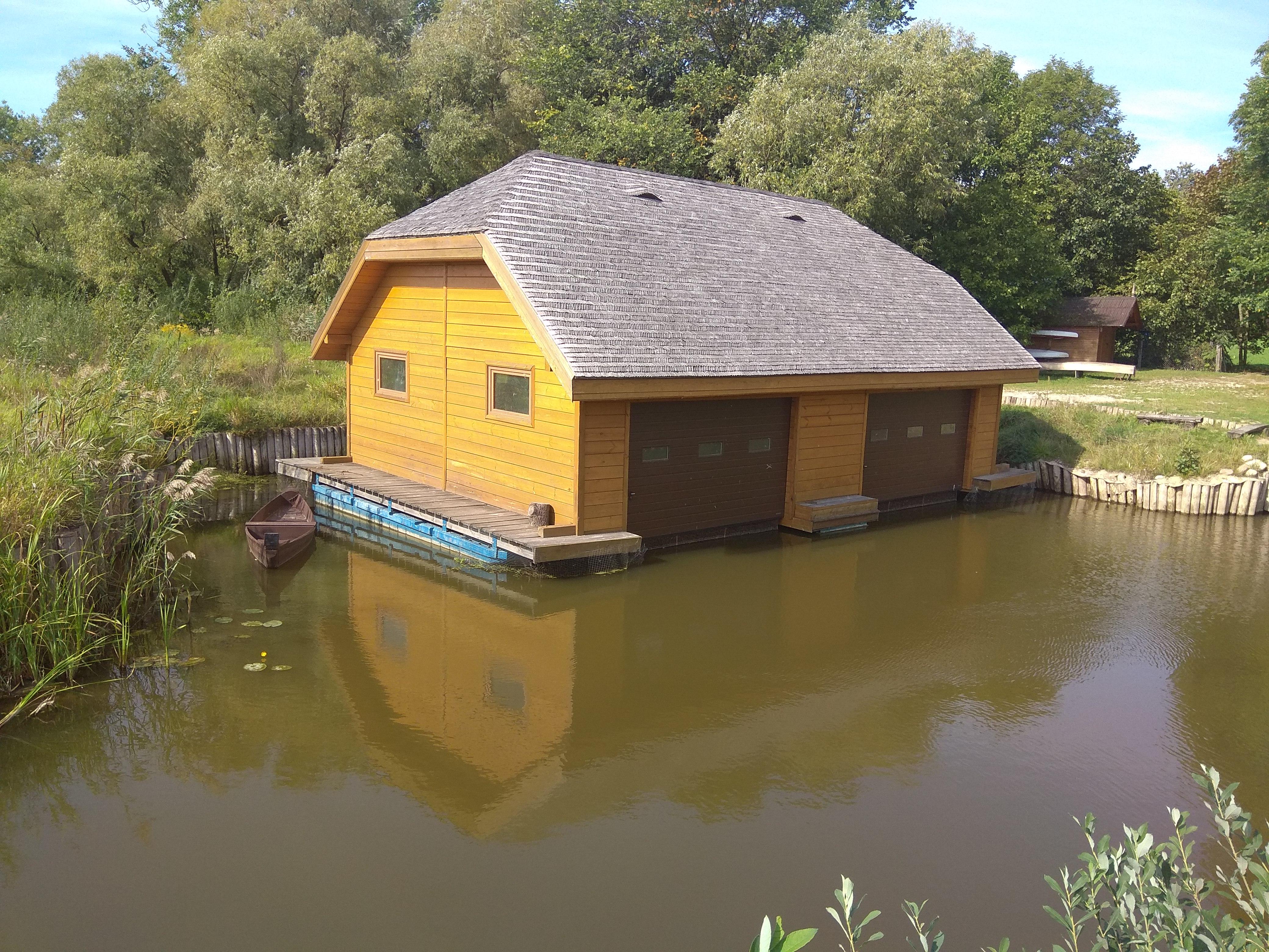 Drewniany, żółty domek osadzony na wodzie, to przystań łodzi strażników Narwiańskiego Parku Narodowego.