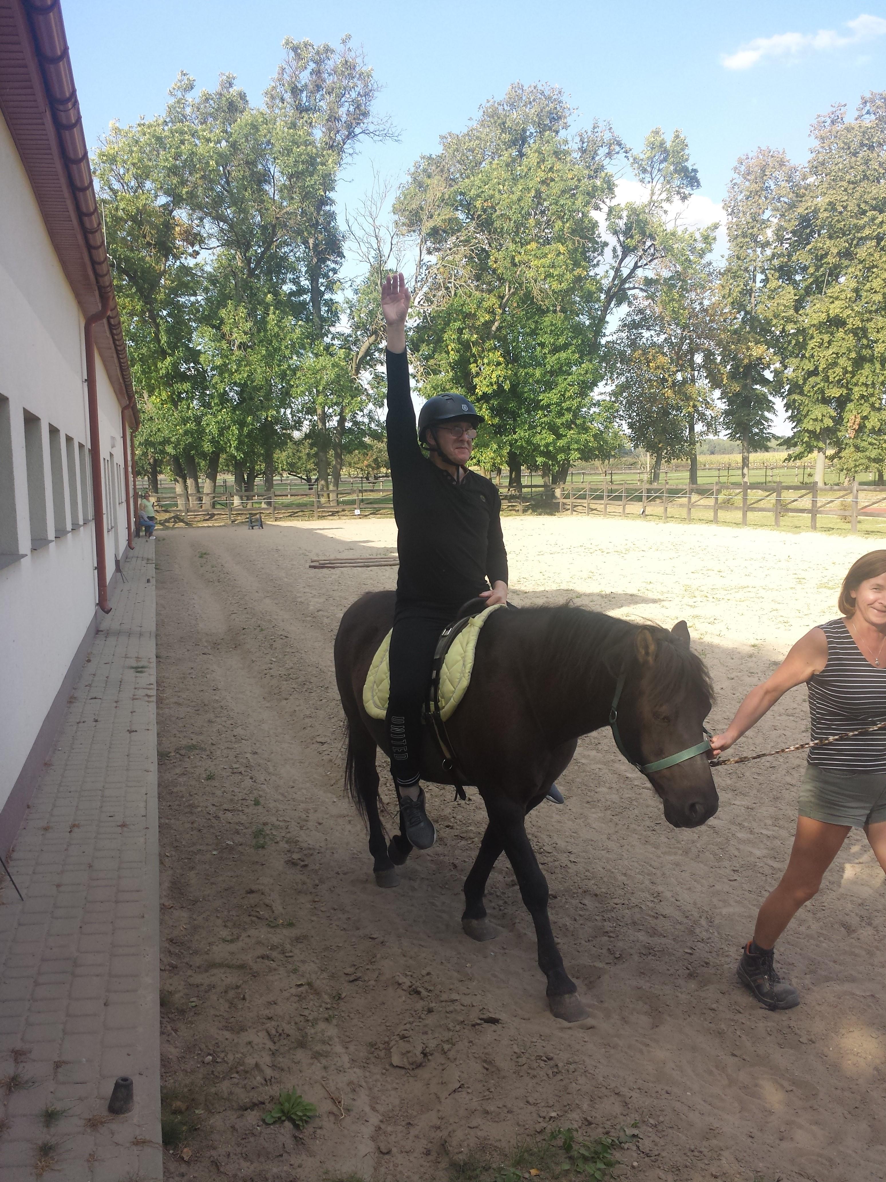 Mężczyzna w okularach, ubrany na czarno, na głowie dżokejka.  Siedzi na koniu prowadzonym przez trenera jazdy konnej i unosi pionowo w górę prawą rękę. Idą wzdłuż budynku, z prawej strony przestrzeń otoczona licznymi drzewami.