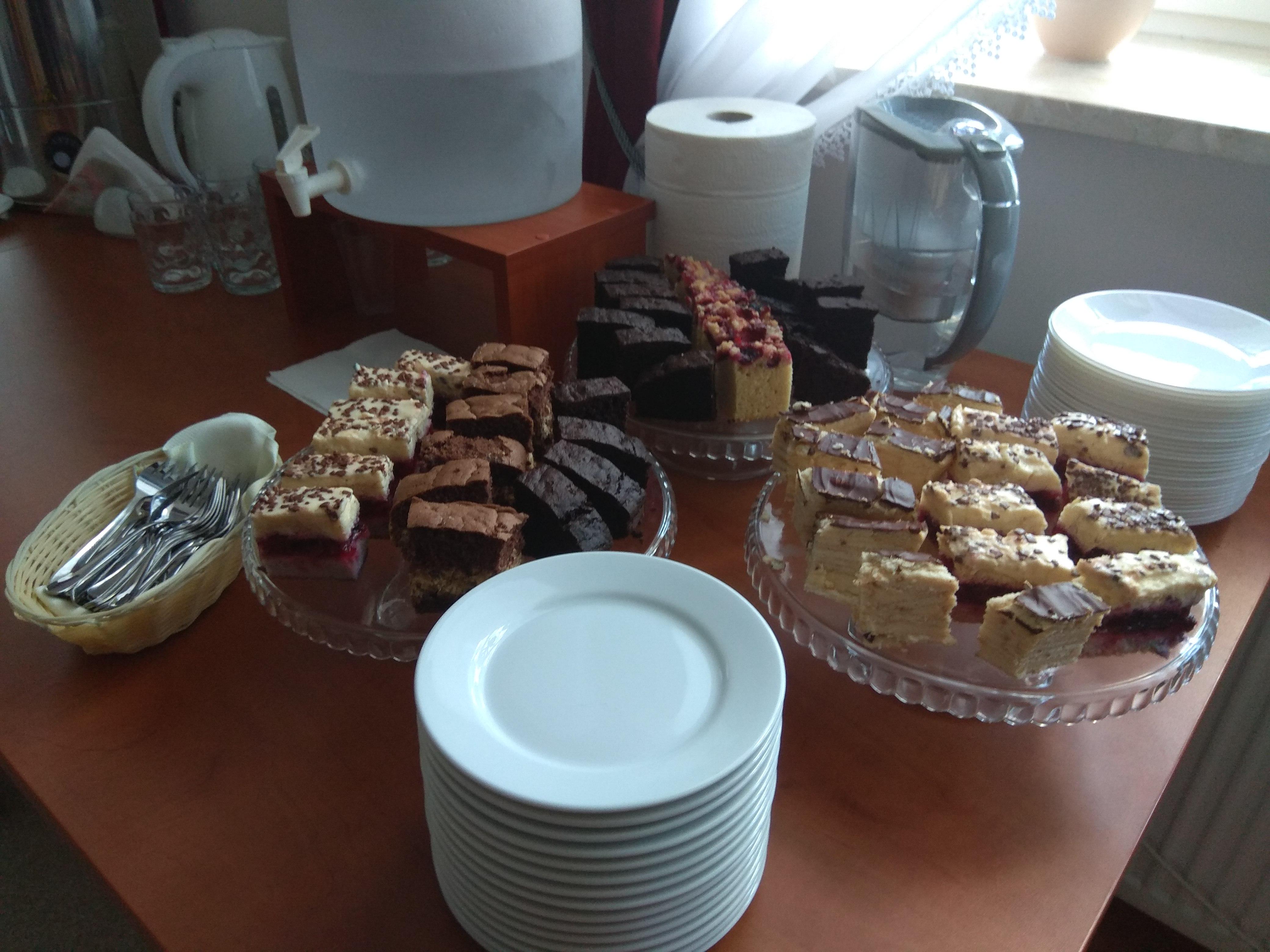 Stół smakołyków. Po szkoleniu dobrze przekąsić coś smacznego. Na zjazdowiczów czeka stół z białą zastawą i dwoma talerzami różnych ciast.