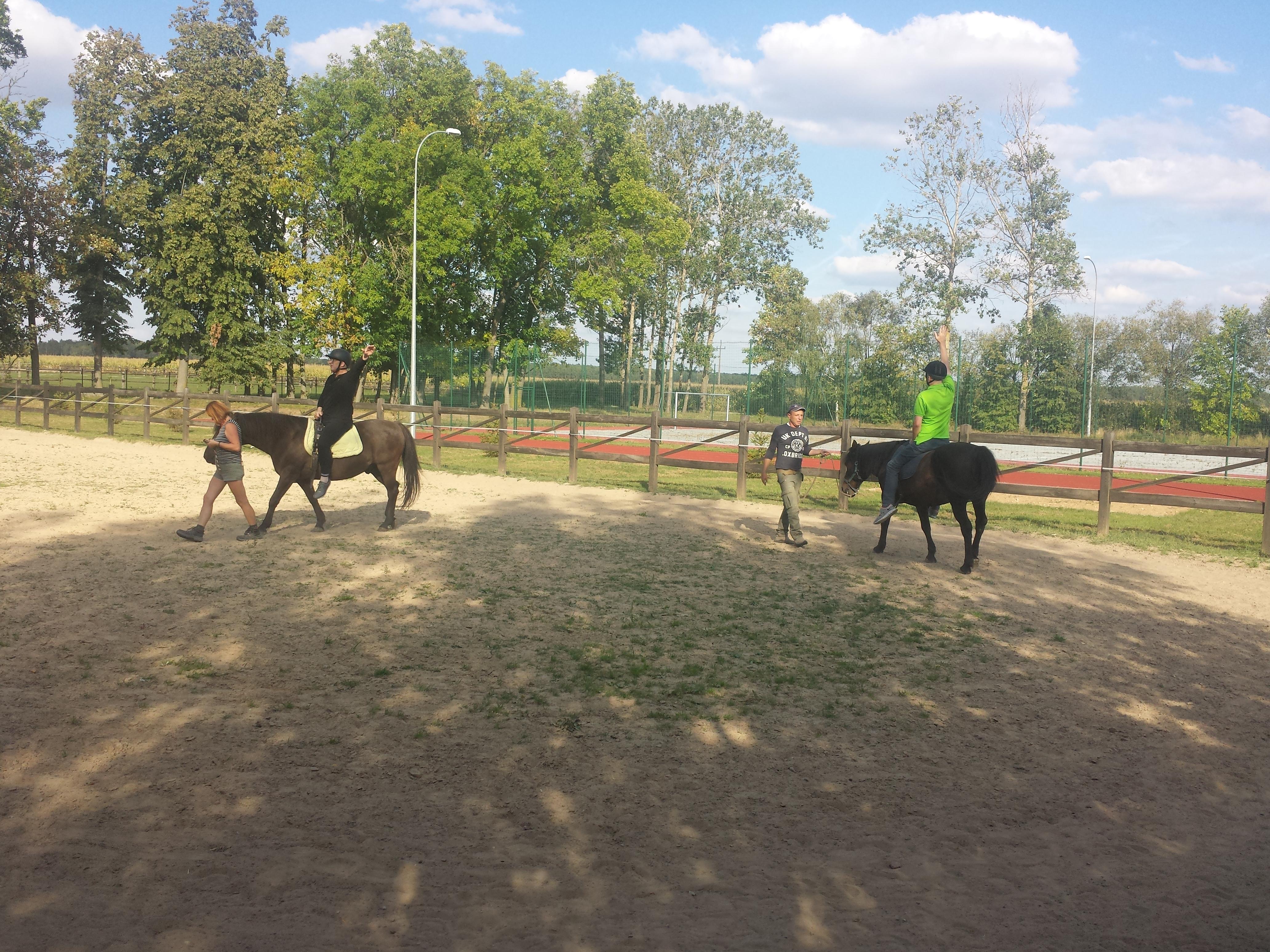 Dwoje uczestników konno. Każdy z nich siedzi na karych koniach prowadzonych na lejcach przez opiekunów. Wokół padoku rosną liściaste drzewa, pełne zieleni.