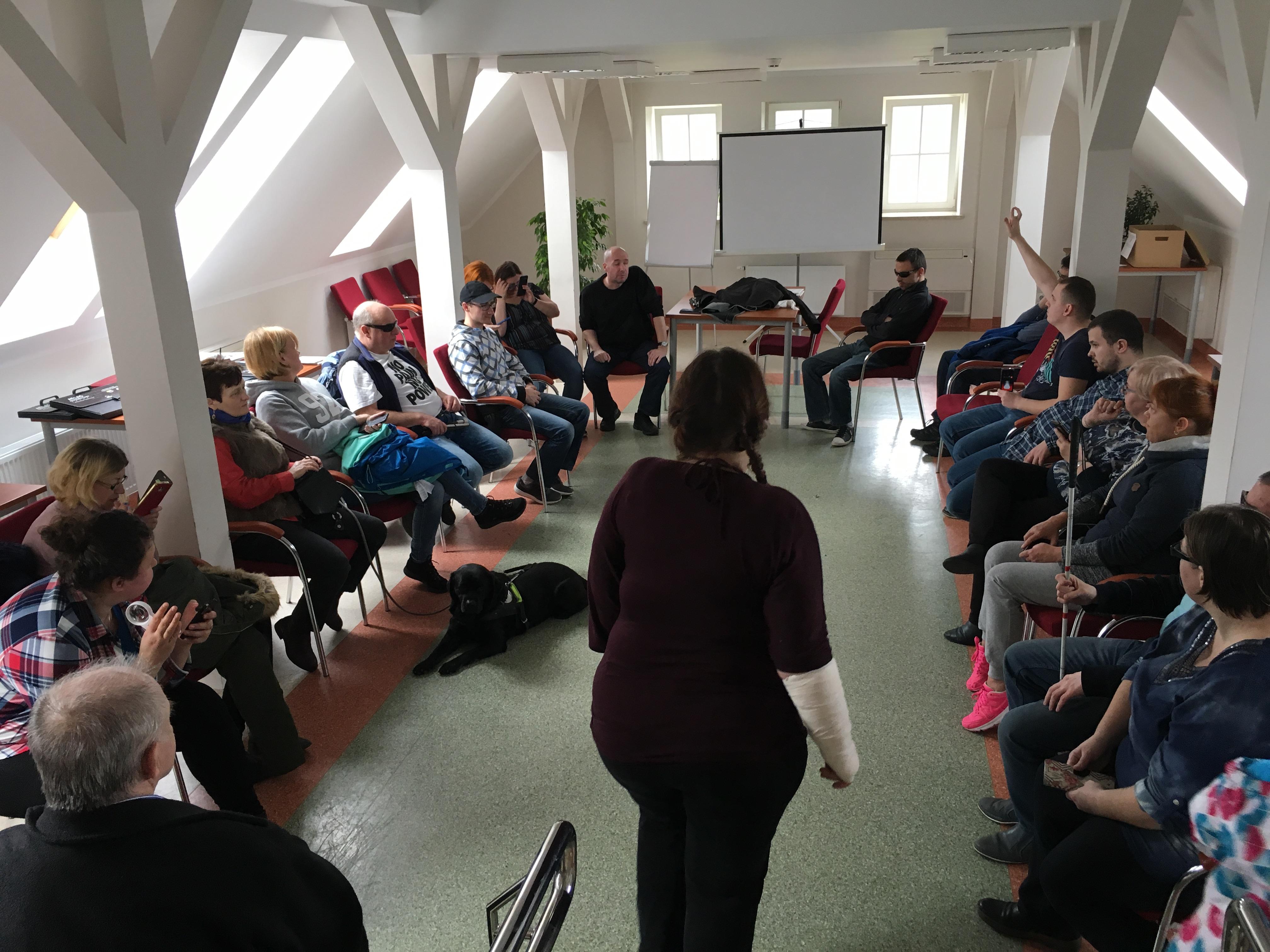 Duża grupa uczestników siedząca w białej Sali na krzesłach ustawionych po owalu, z przodu widoczna stojąca sylwetka   kobiety w warkoczach,  ubranej w ciemną bluzkę i spodnie , na dalszym planie jeden z uczestników podnosi wysoko rękę. Na tle  jednej z białych ścian, wszystkie z oknami, stoi tablica.