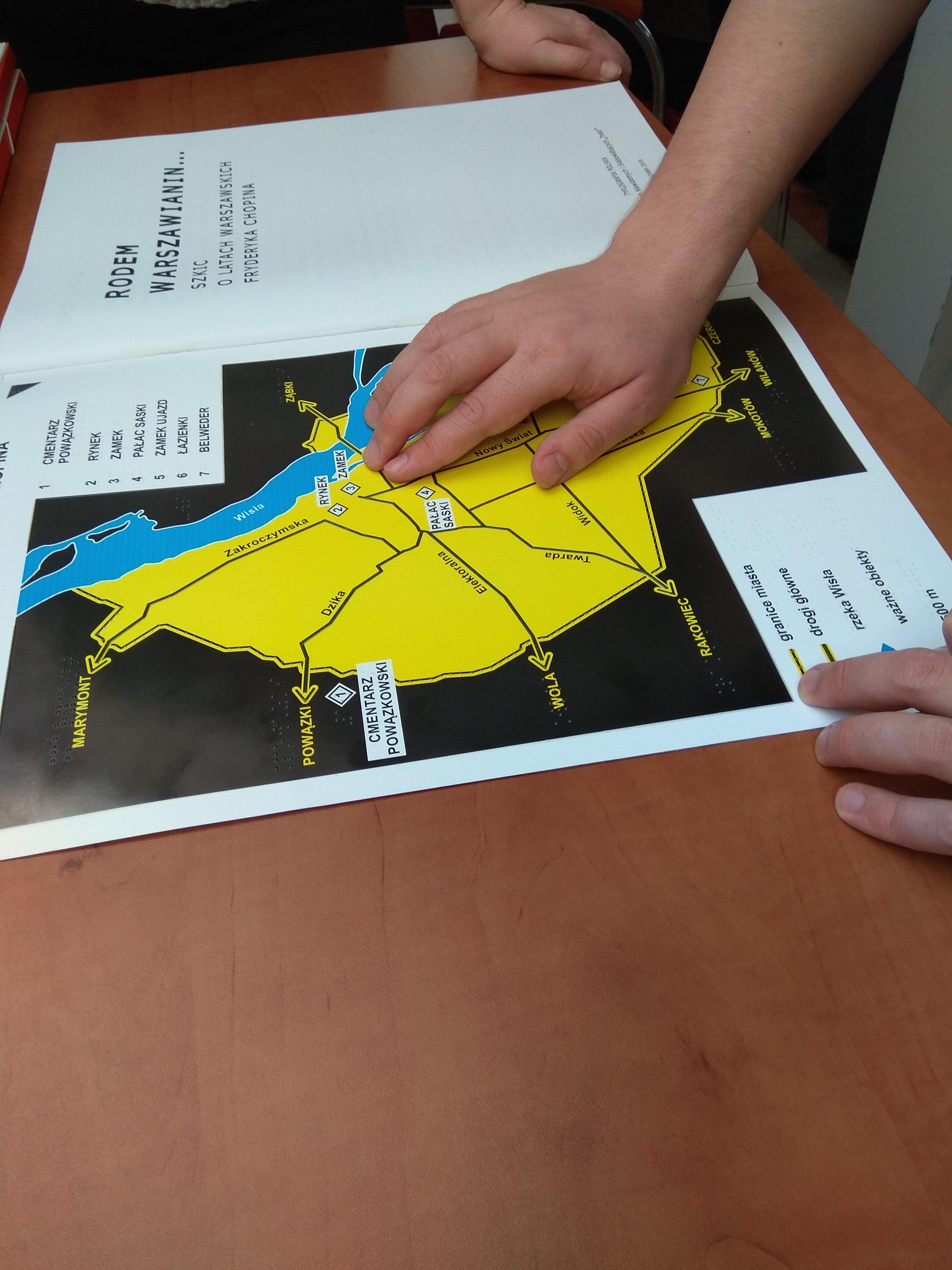 W zbliżeniu dłoń osoby czytającej dotykiem mapę.