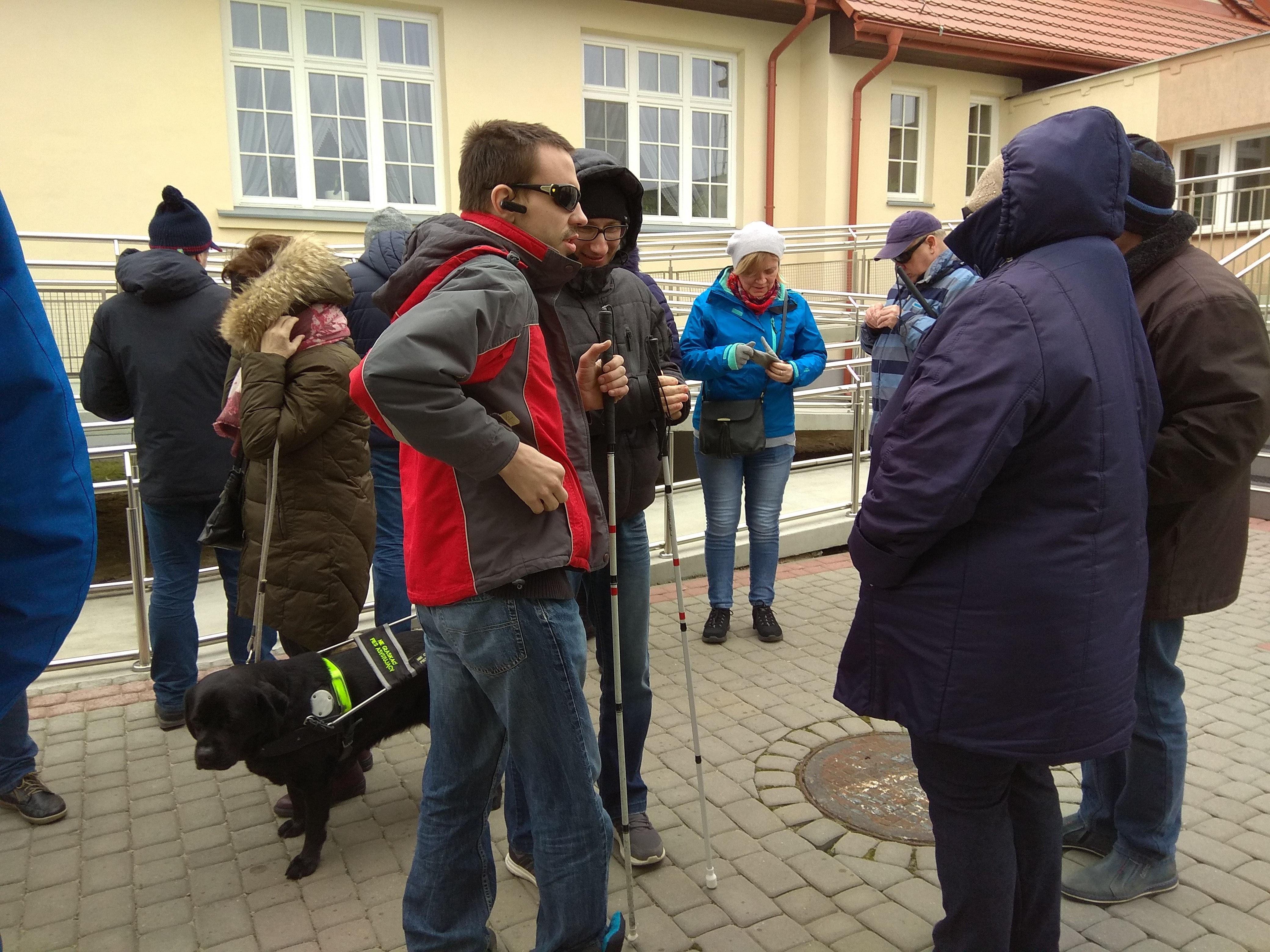 Panie i panowie ubrani w kurtki stojący przed budynkiem ośrodka, kilkoro z nich z laską, a pośród nich ciemnobrązowy pies – przewodnik.
