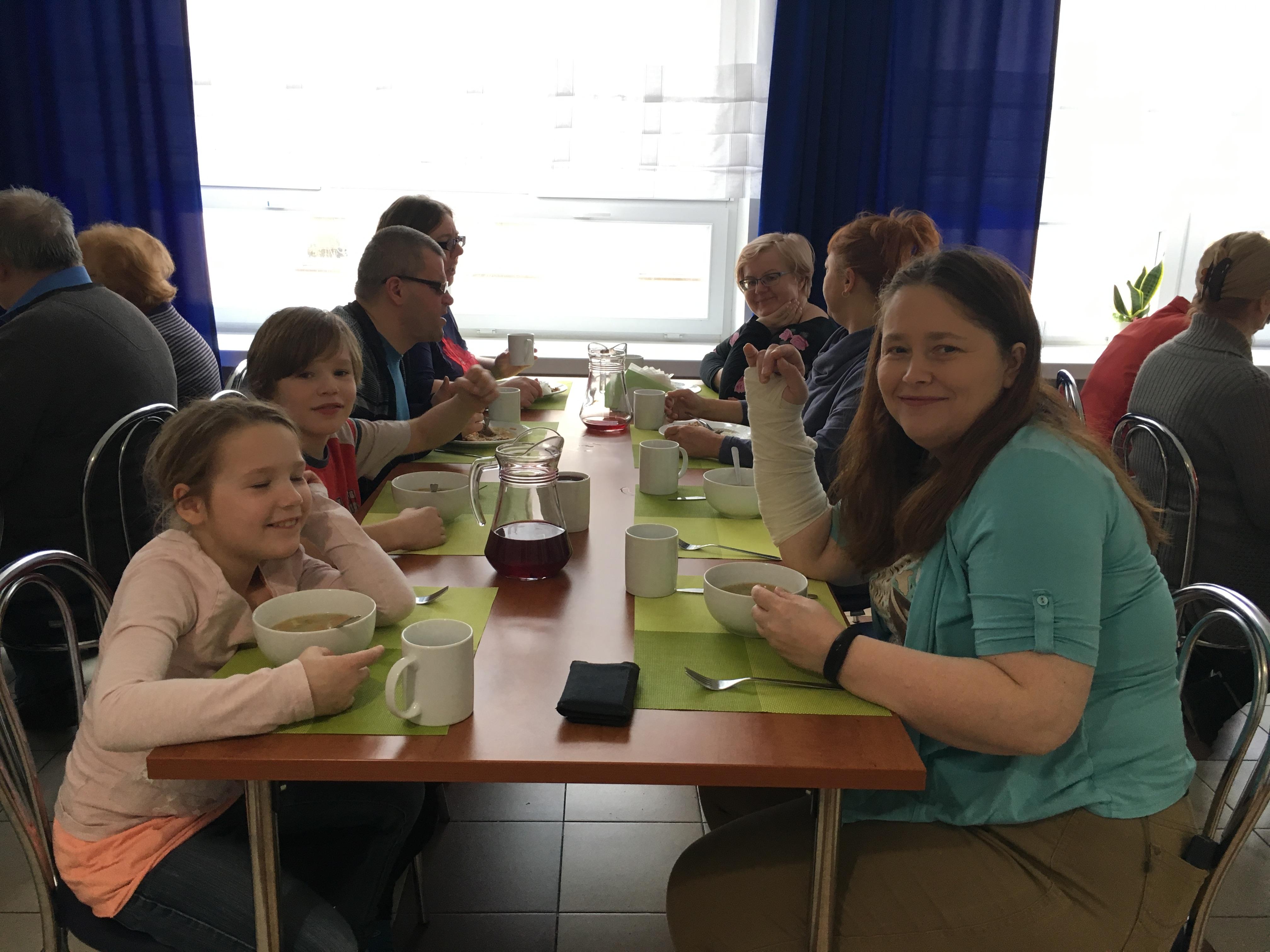 Siedmioro gości podczas posiłku, siedzący przy stole z białą zastawą. Na środku stołu dzbanek przeźroczysty z napojem, z prawej strony stołu uśmiechnięta uczestniczka w niebieskiej bluzce i długich kasztanowych włosach.