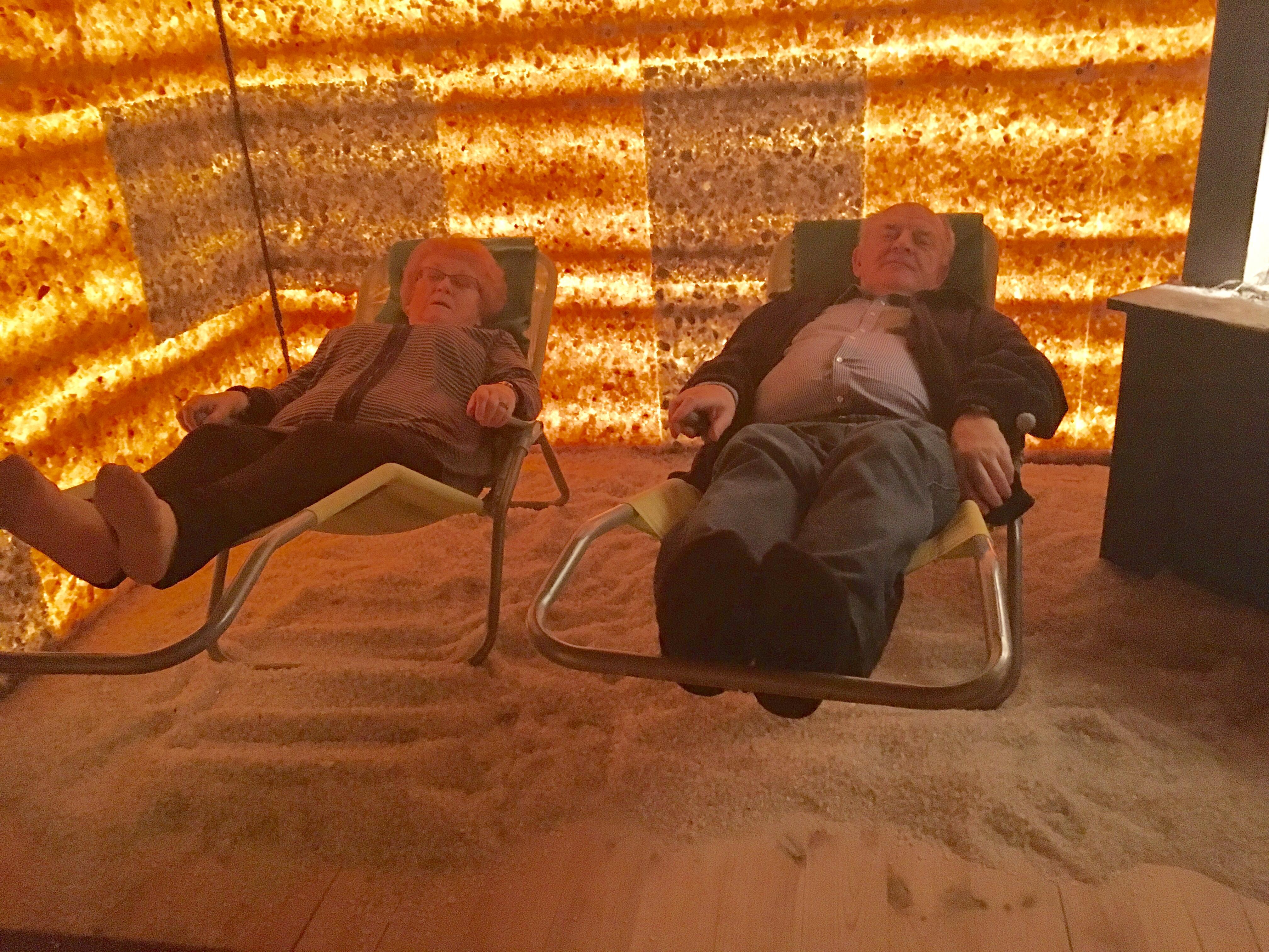W grocie solnej – dwaj panowie relaksujący się na leżakach w grocie solnej. Pomieszczenie bez okien , ściany podświetlane w brązowo-rudej kolorystyce.