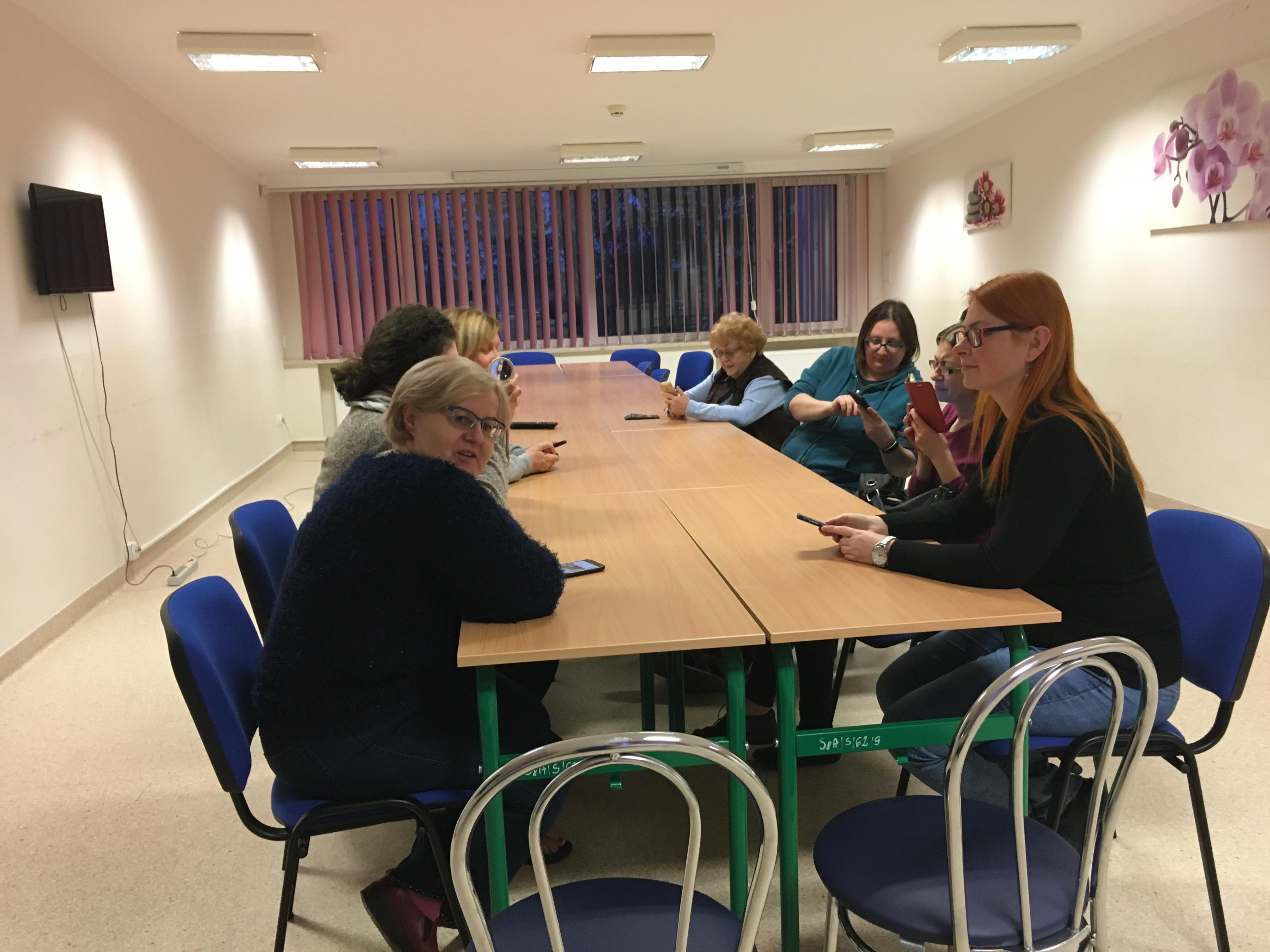 Kilka uczestniczek podczas szkolenia, siedzą na niebieskich krzesłach, przy złączonych ze sobą czterech stołach, w białej Sali z kasetonowym oświetleniem. Z lewej wiszący na ścianie telewizor, z prawej dwa obrazki z tematyką kwiatową, a po środku okna przesłonięte wertykałem.