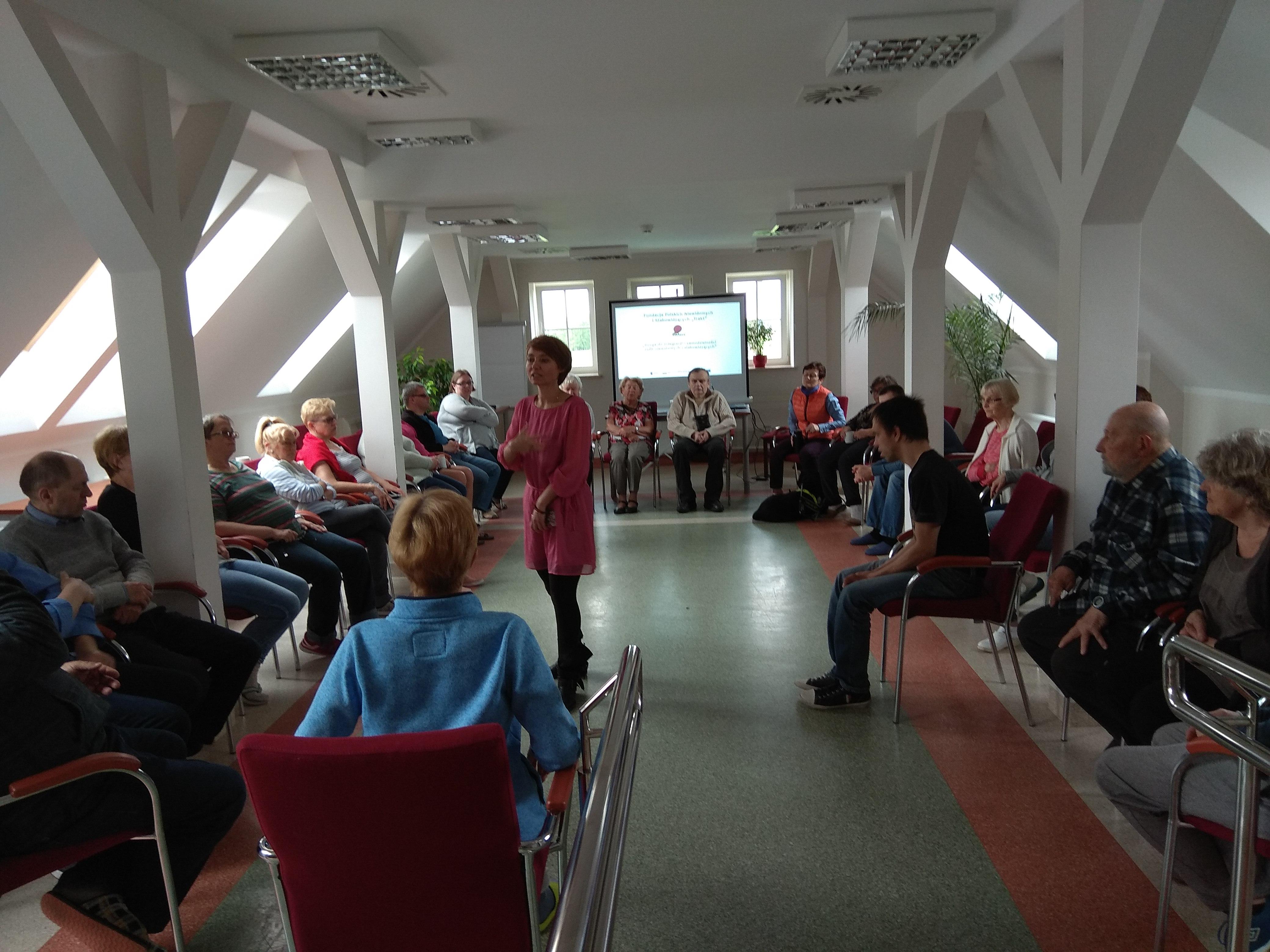 Kreacji wizerunku ciąg dalszy – tym razem wizażystka stoi pośrodku siedzących na czerwonych fotelach gości ośrodka. Sala dobrze oświetlona naturalnym światłem wpadającym przez, ukośne okna usytuowane po dwóch stronach pomieszczenia.