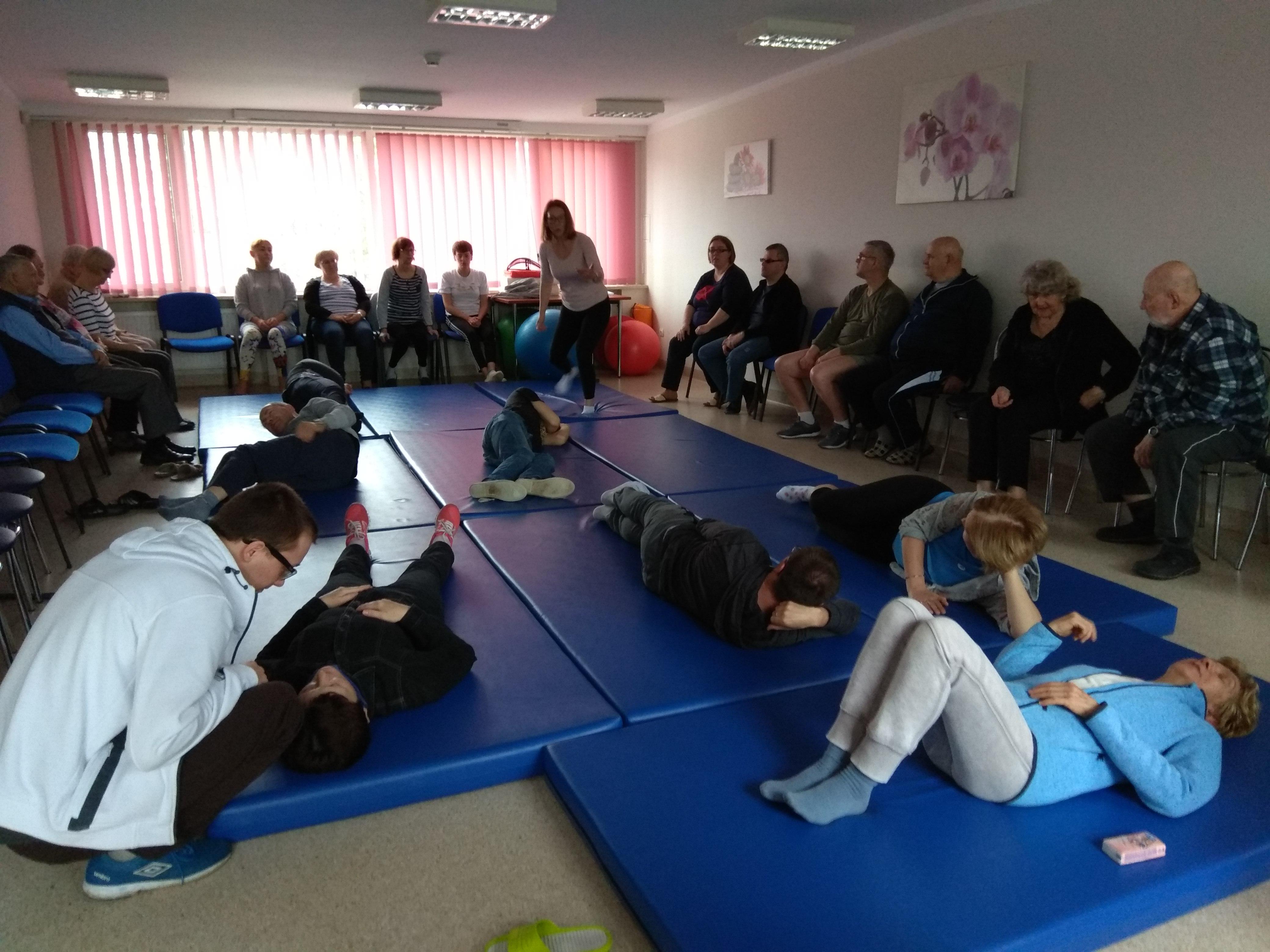 Kilka osób ćwiczących w pozycji leżącej na plecach. Z lewej strony przy jednej z nich fizjoterapeutka w białej bluzie udzielająca indywidualnych wskazówek.
