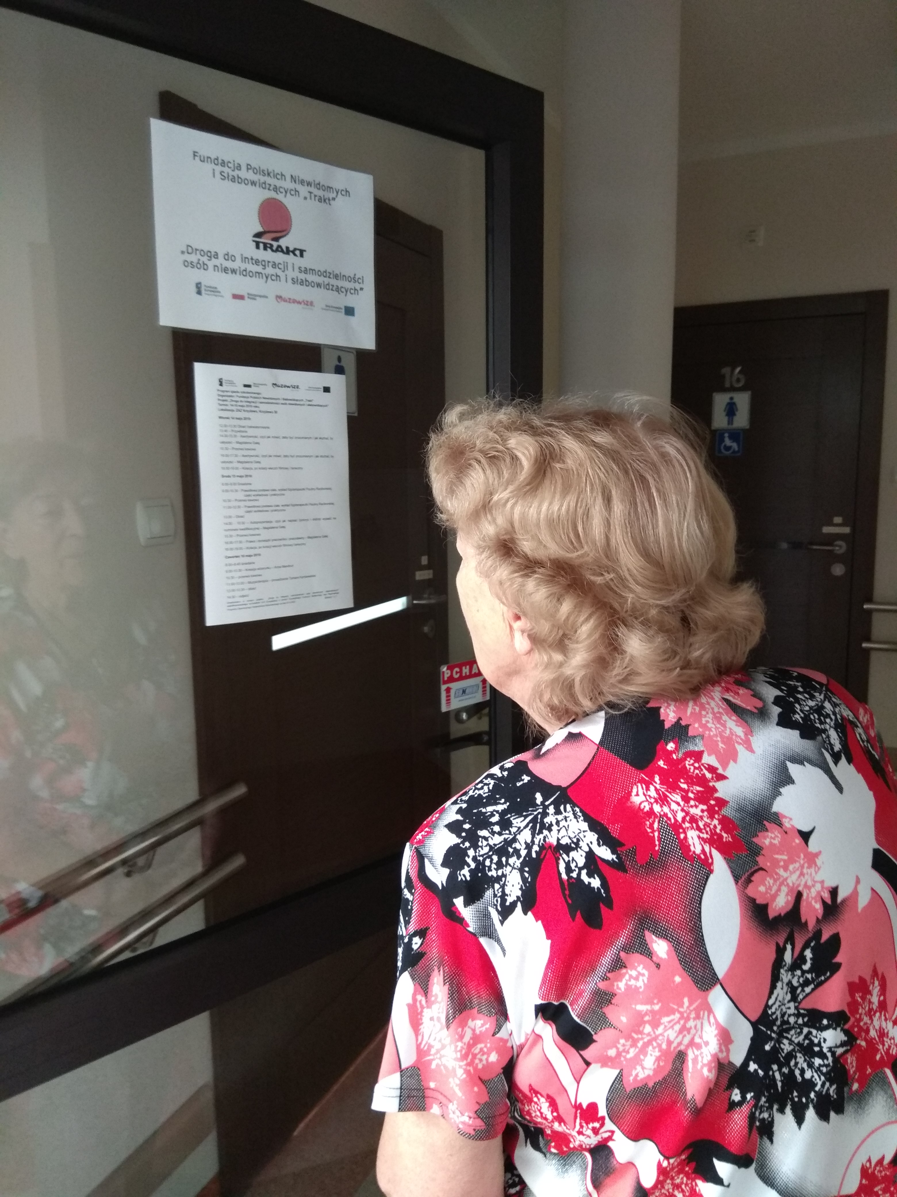 Blondynka w lekko kręconych włosach i biało – malinowo -czarnej bluzce z krótkim rękawem czytająca wiszący na ścianie plan zjazdu.