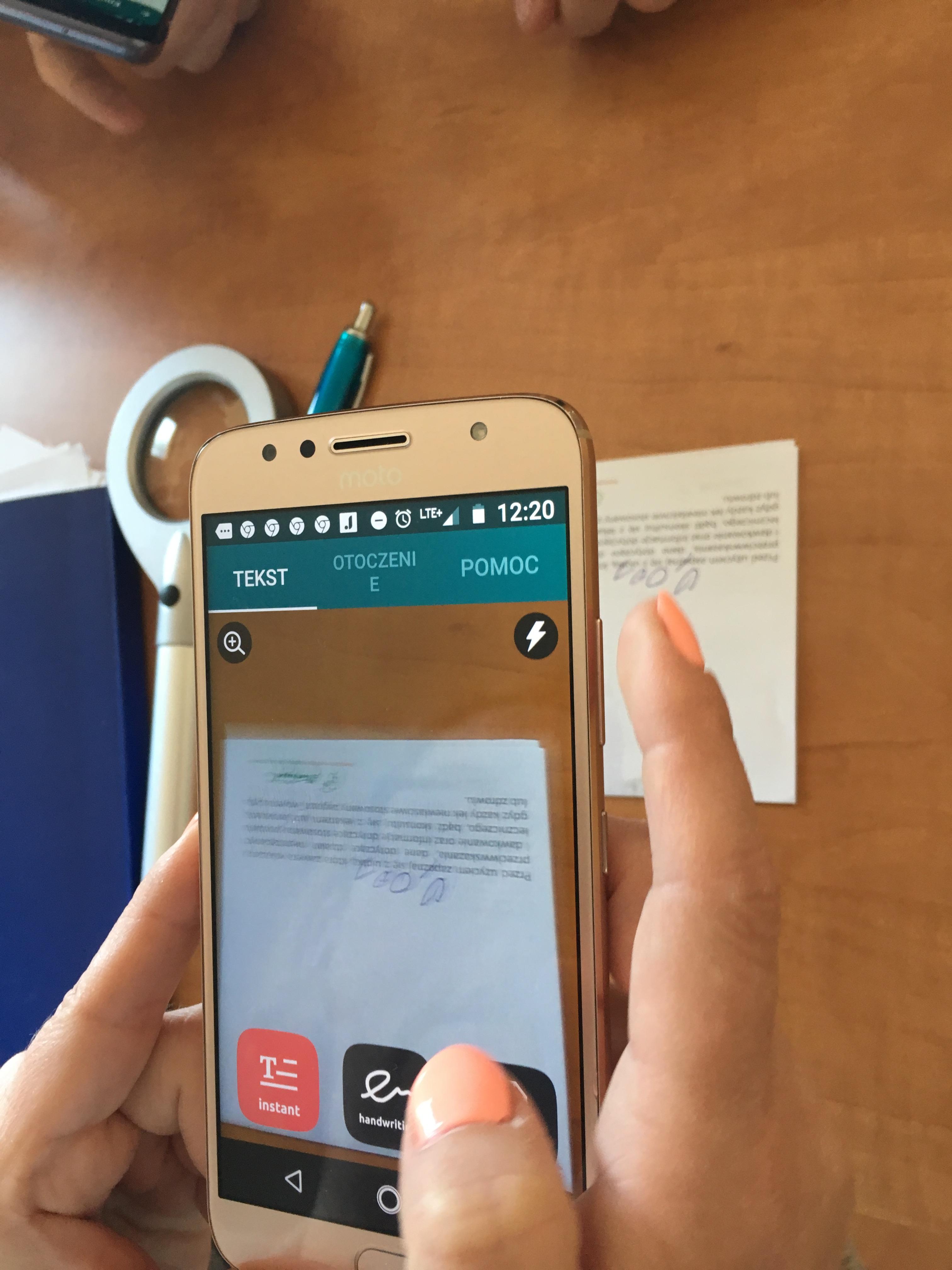 Smartfon z białą ramką w kobiecych dłoniach, pod nim widoczna biała lupa.