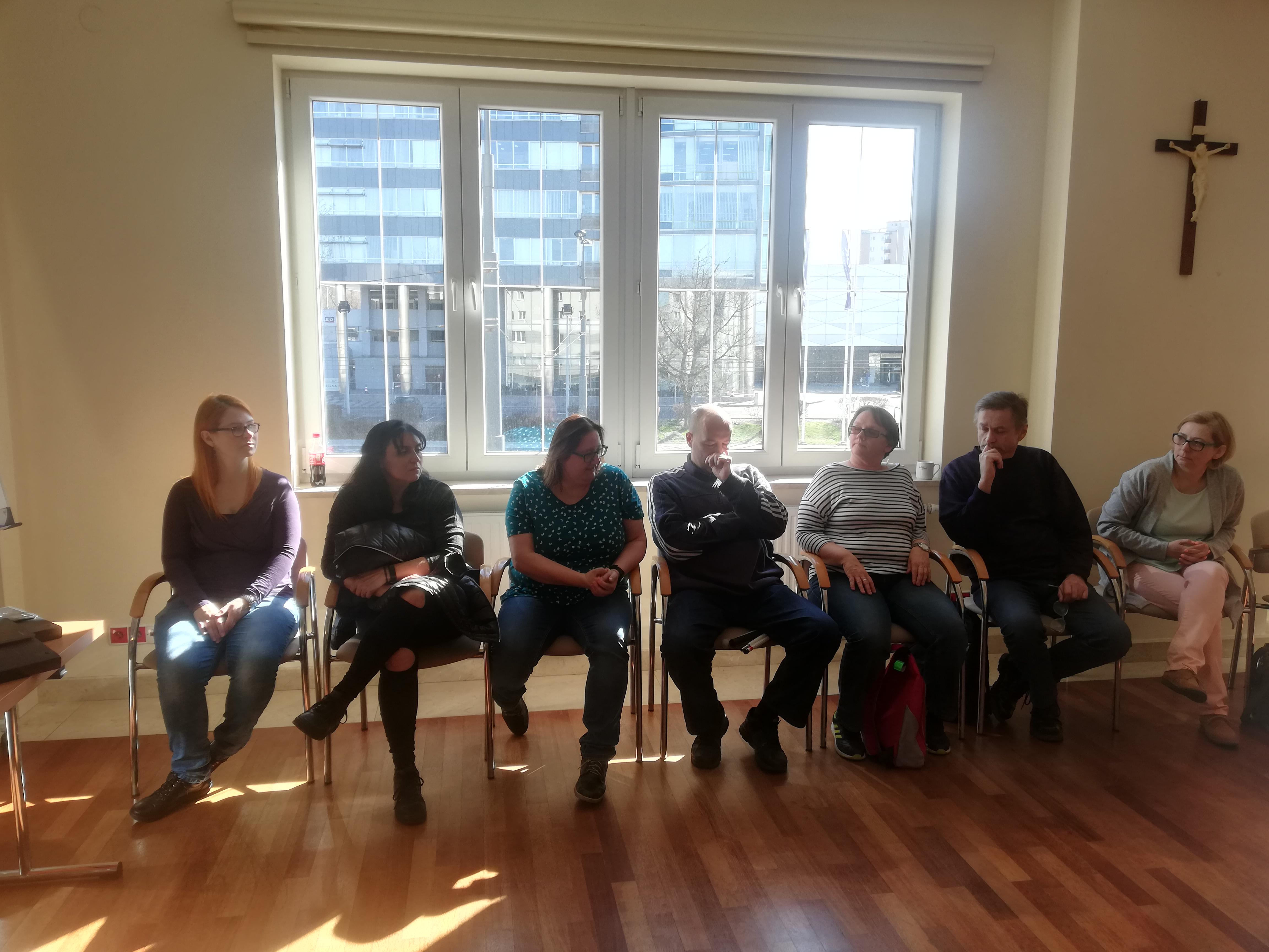 Uczestnicy siedzący na tle dużego okna, za którym prezentuje się wysoki biurowiec.