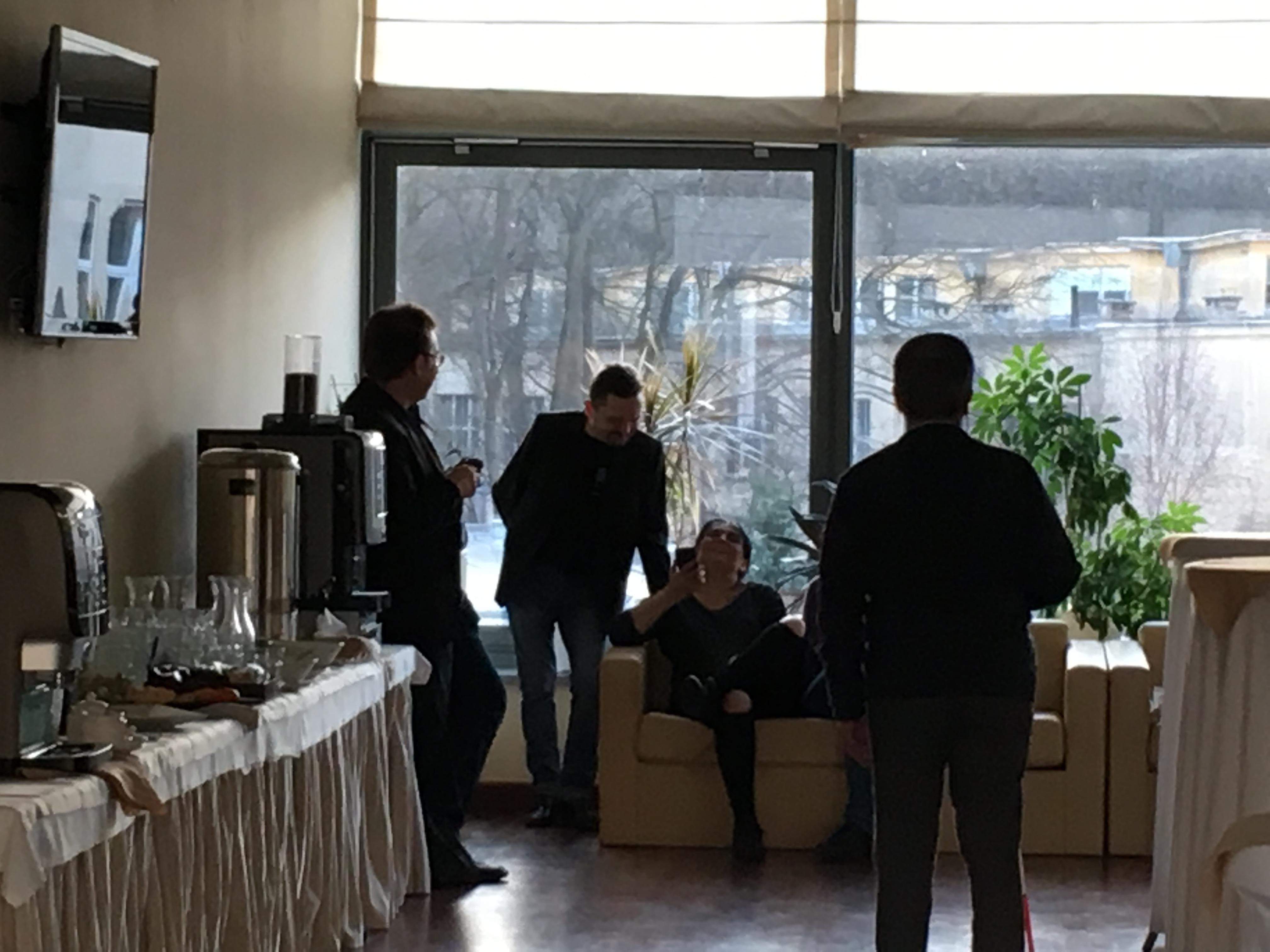 Trzej panowie w garniturach, stoją na tle dużego okna, obok na jasnej sofie siedzi pani uczestniczka zjazdu. Z prawej strony na parapecie stoją soczysto zielone rośliny w donicach, jedna duża i dwie mniejsze. Z lewej strony stół przykryty jasnym materiałem opadającym do podłogi, ustawiony wzdłuż ściany. Na stole expres do kawy, duży termos oraz zastawa z białymi filiżankami, talerzykami i przeźroczystymi szklankami.