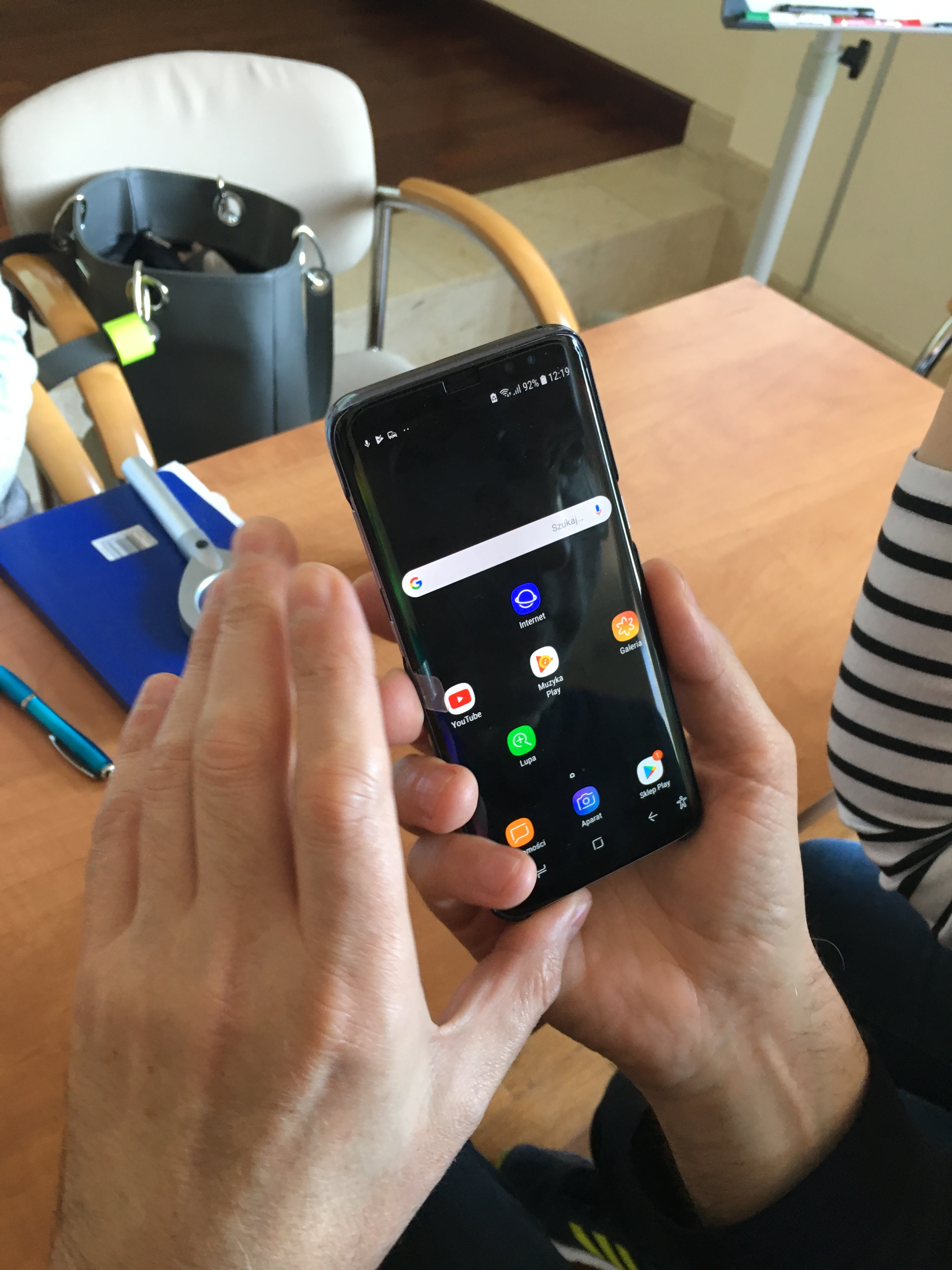 W zbliżeniu dwie dłonie trzymające czarny smartfon, nad jasnobrązowym stołem, na którym leżą niebieski długopis i etui.