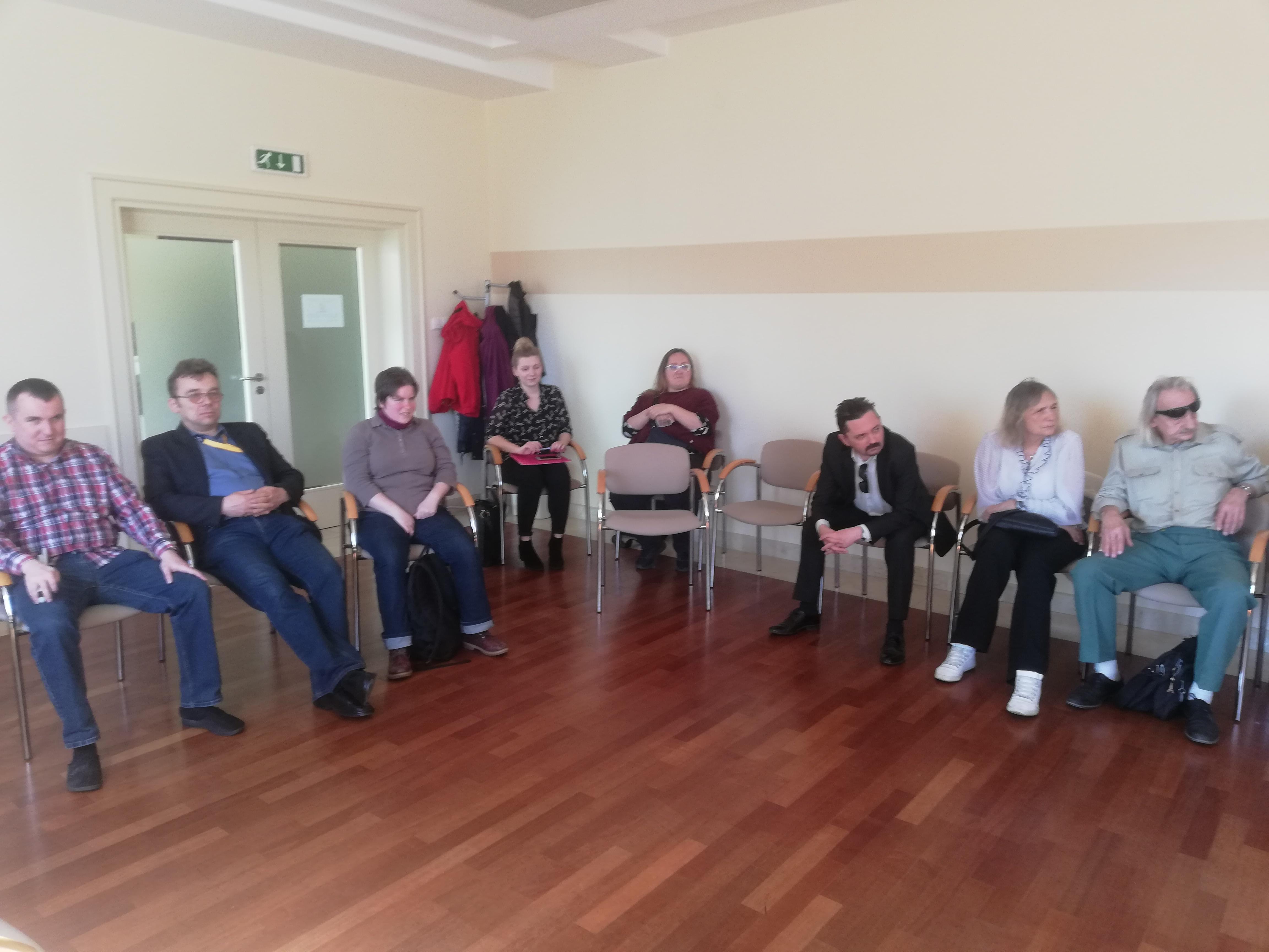 Grupa uczestników siedząca na krzesłach ustawionych wzdłuż białych ścian, w lewym rogu stoi wieszak z kilkoma kurtkami. Obok niego po lewej widoczne zamknięte, dwuskrzydłowe, przeszklone drzwi. Podłoga z brązowych paneli.
