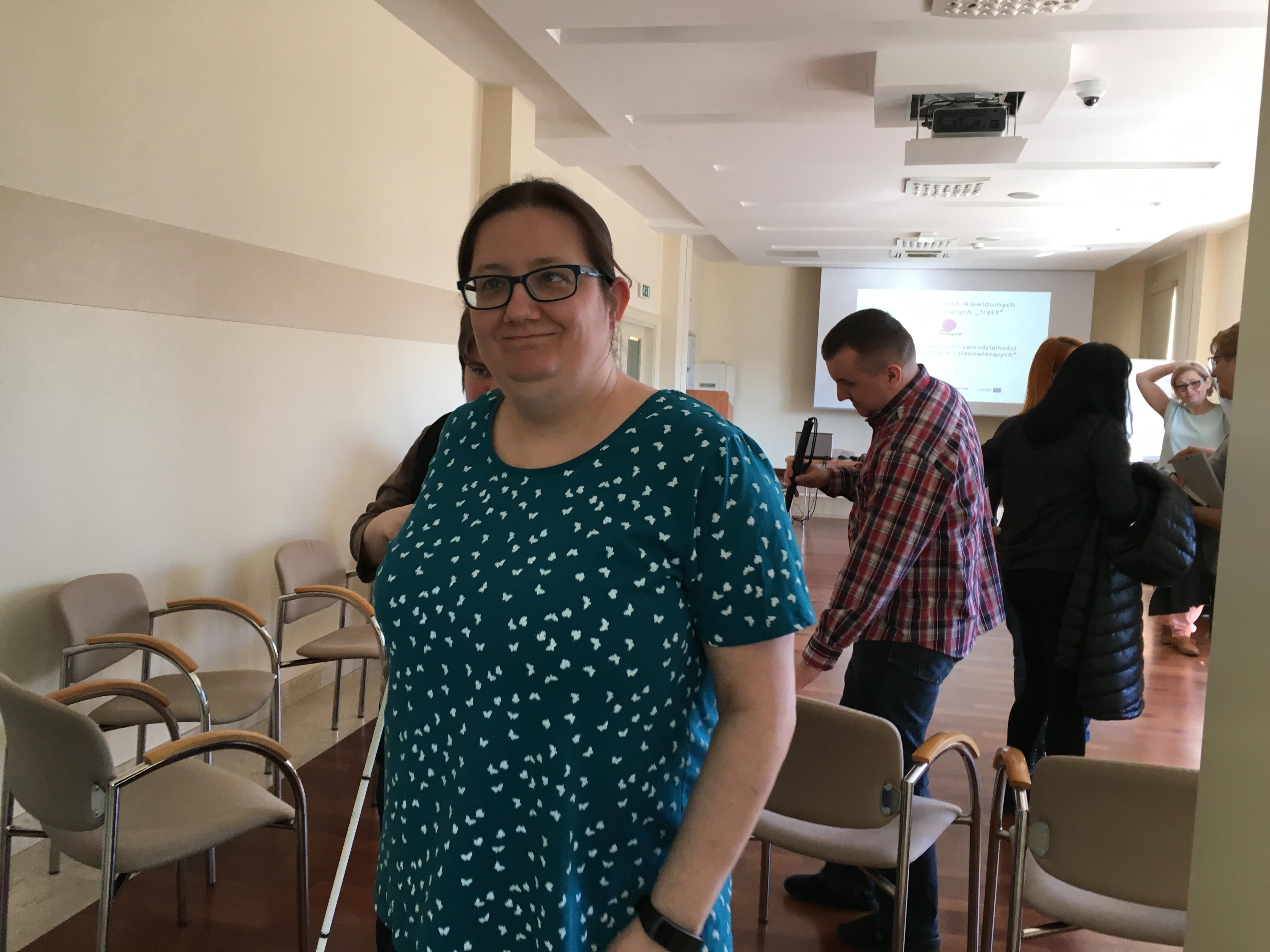 Kilka osób opuszczających salę konferencyjną,  w której znajdują się białe, tapicerowane  krzesła. Na pierwszym planie lekko uśmiechnięta brunetka w okularach z ciemnymi oprawkami. Ubrana jest w niebieską bluzkę w białe groszki. Trzyma w ręku laskę.