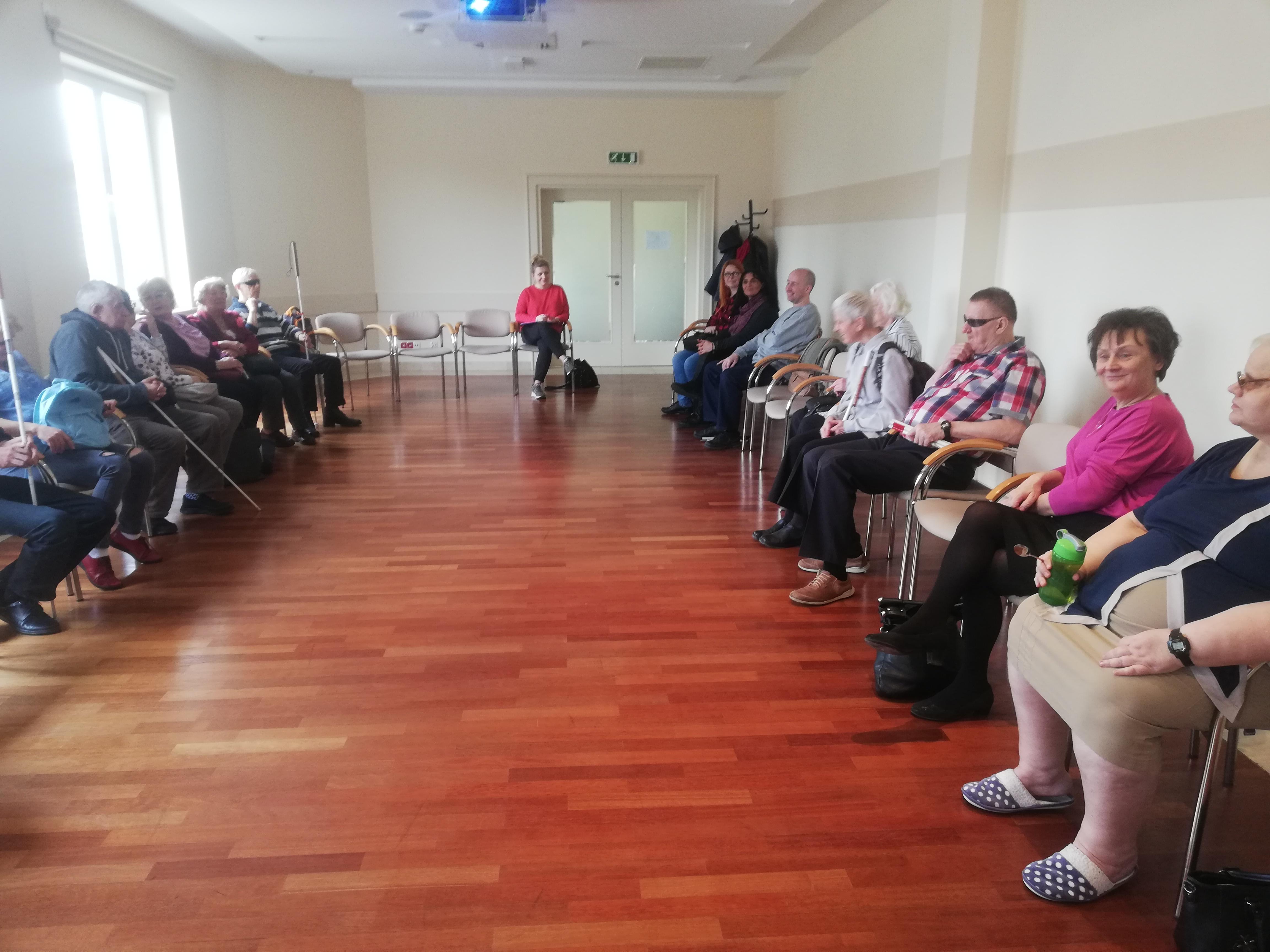 Duża sala konferencyjna z białymi ścianami i podłogą z prostokątnymi panelami w kolorze kasztanowym. W pomieszczeniu na krzesłach ustawionych wzdłuż ścian siedzą uczestnicy szkolenia. Uwagę zwraca siedząca z prawej strony subtelnie uśmiechnięta pani w średnim wieku ubrana w malinową bluzkę. Na tle przeszklonych drzwi siedzi blondynka w upiętych do góry włosach, w czerwonej bluzce.