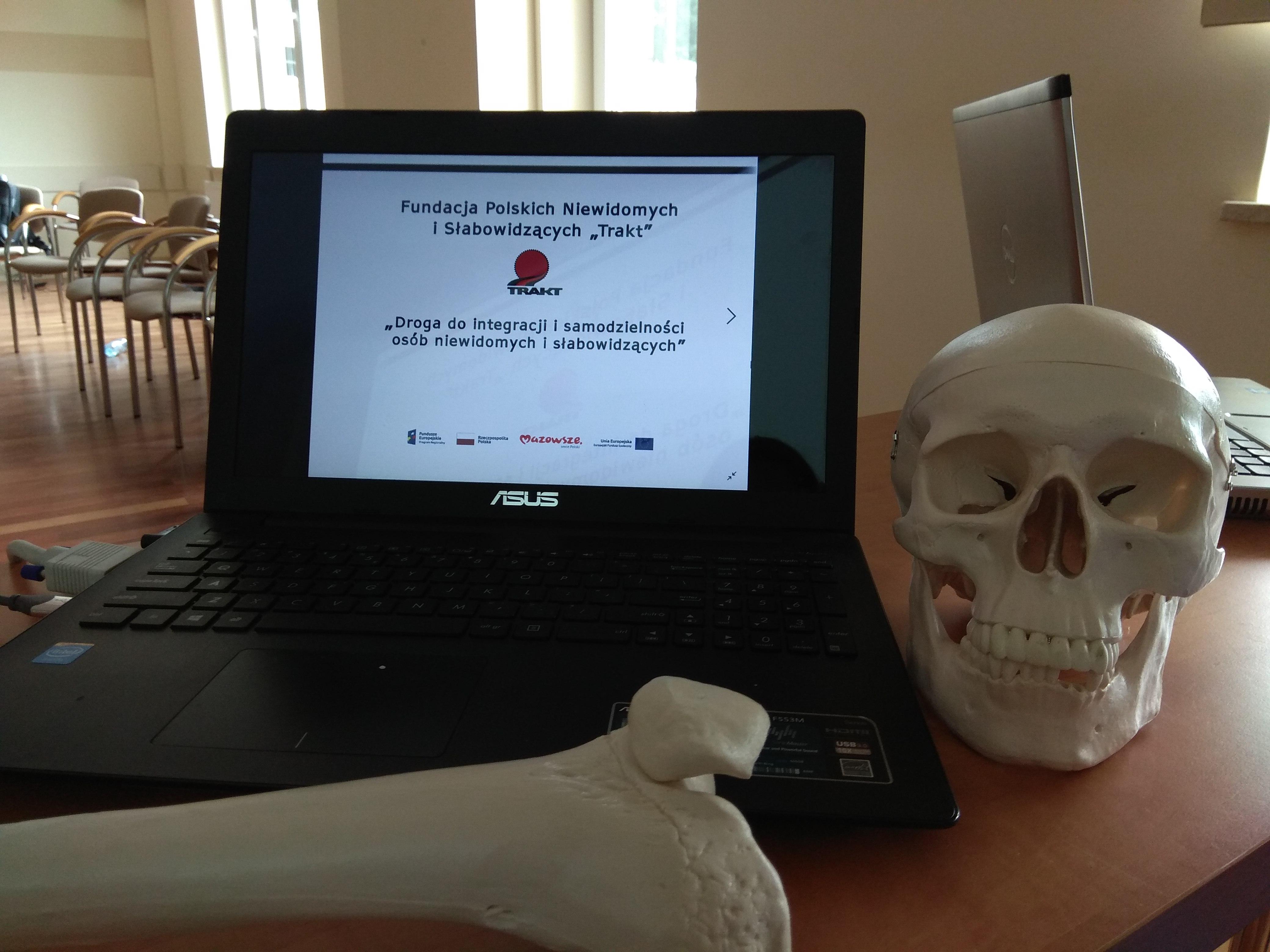 Zbliżenie na laptop z wyświetlonym na ekranie logo fundacji, a obok niego z prawej strony widoczny model czaszki.