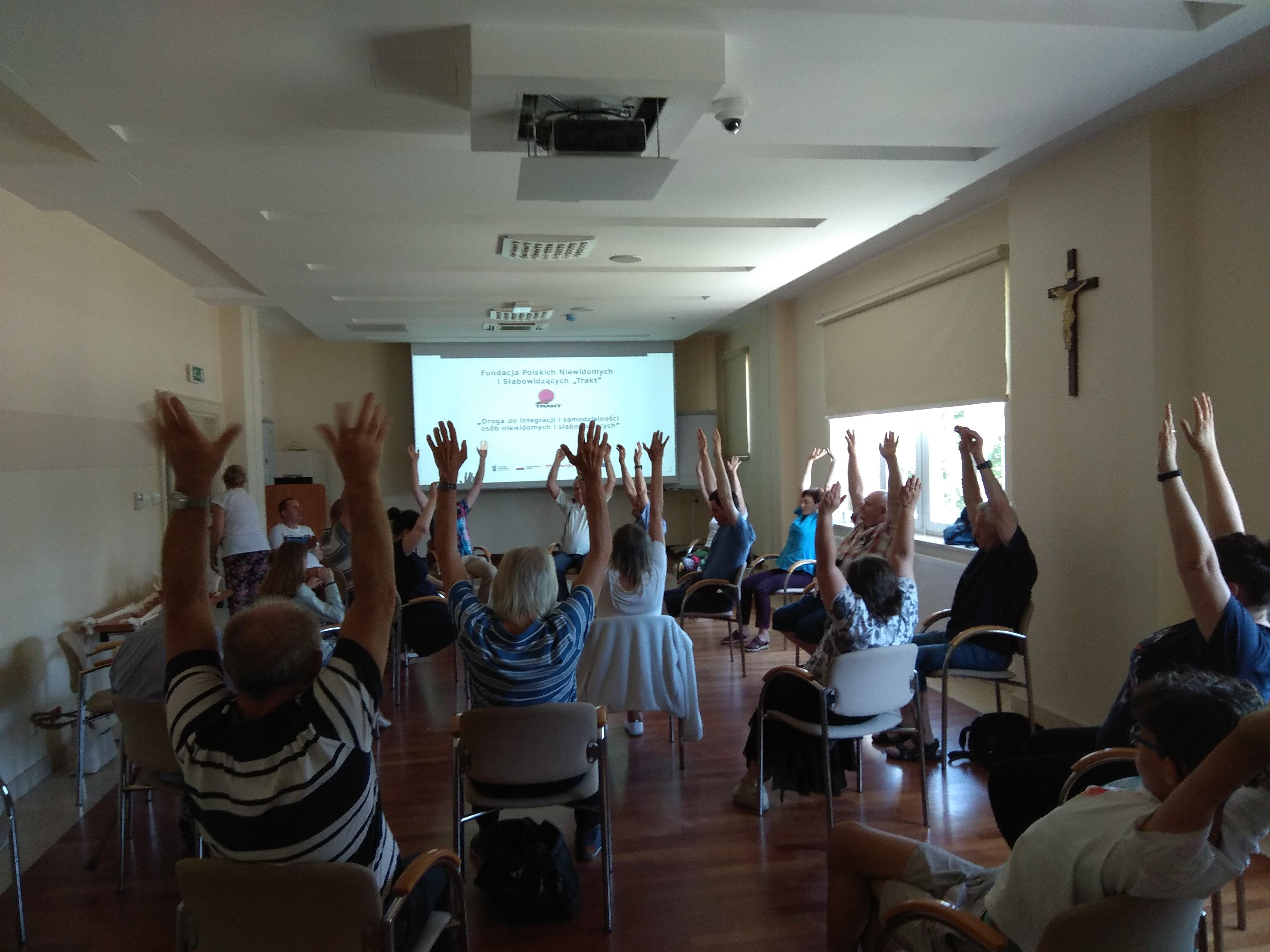 Zjazdowicze praktykujący ćwiczenia na siedząco, mają obie ręce podniesione wysoko w górę. Z prawej strony na białej ścianie wisi brązowy krzyż.