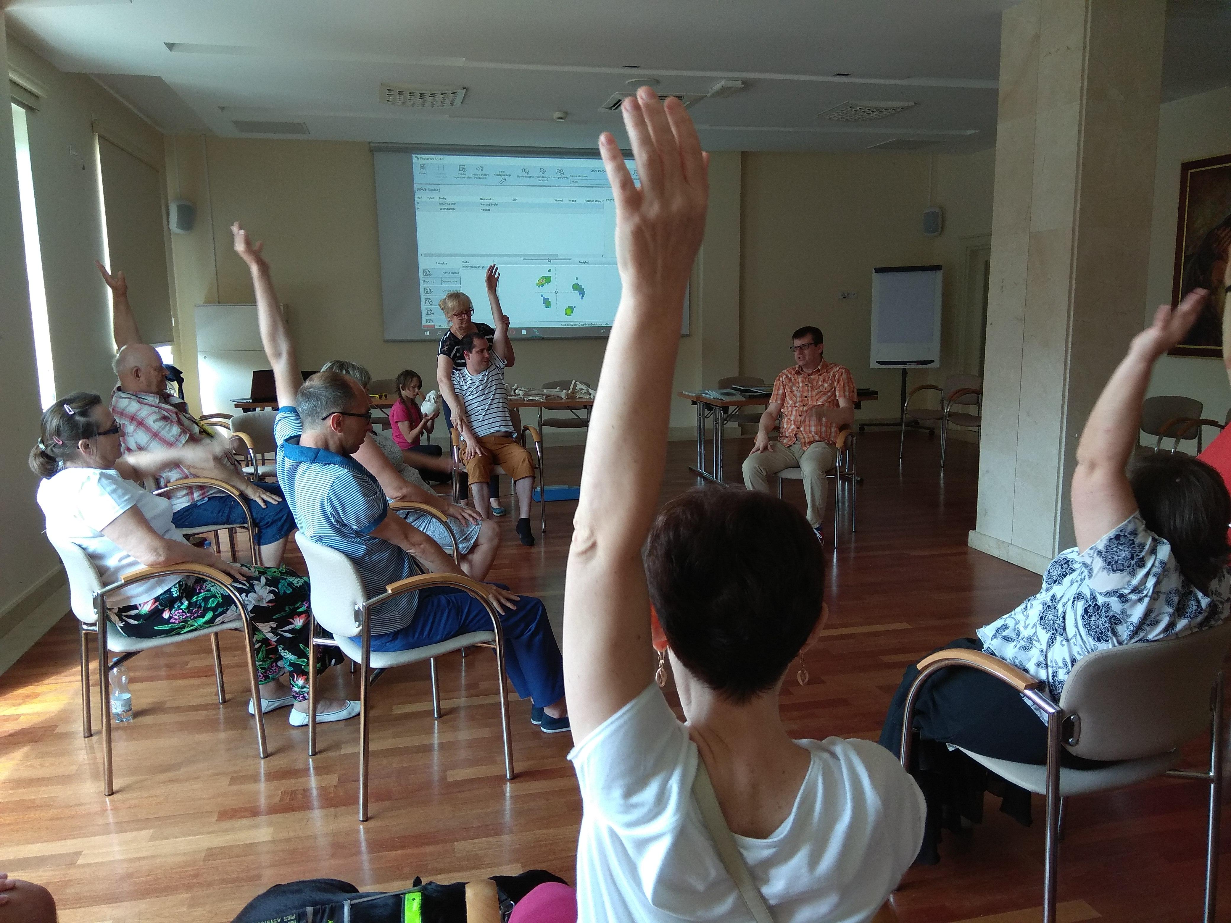 W sali z beżowymi ścianami zjazdowicze wykonują ćwiczenia siedząc na krzesłach ustawionych w luźnym okręgu. Wszyscy w unoszą w górę wyprostowaną lewą rękę.