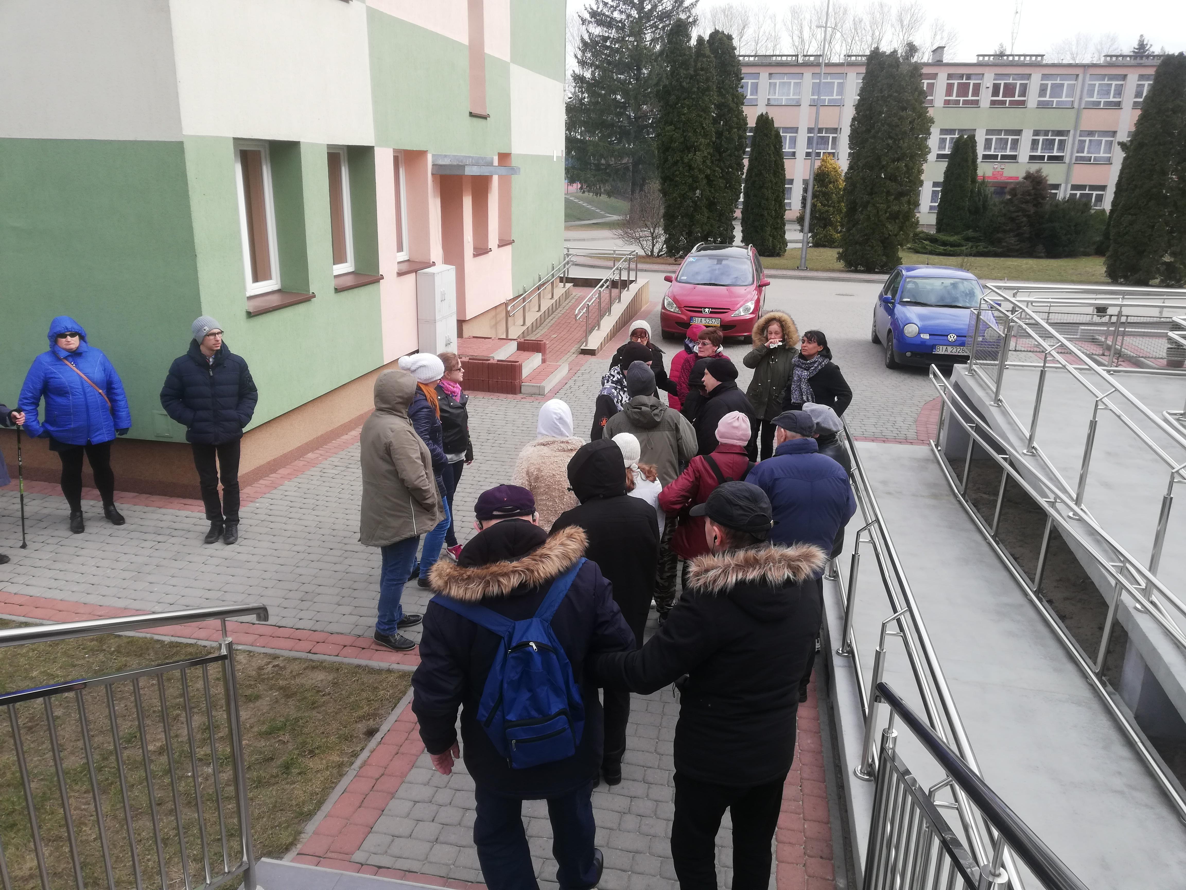 Grupa uczestników w kurtkach wiosennych podczas wychodzenia z budynku, niektórzy z nich w czapkach i kapturach, z boku widoczny zjazd dla wózkowiczów z metalowymi barierkami, z przodu czerwony i niebieski samochód
