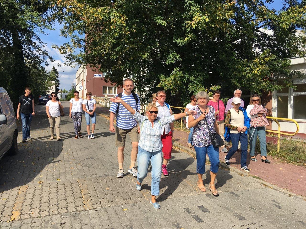 Uczestnicy zjazdu w drodze na bydgoską Starówkę, jedna z pań w radosnym uniesieniu z rękami skierowanymi ku górze
