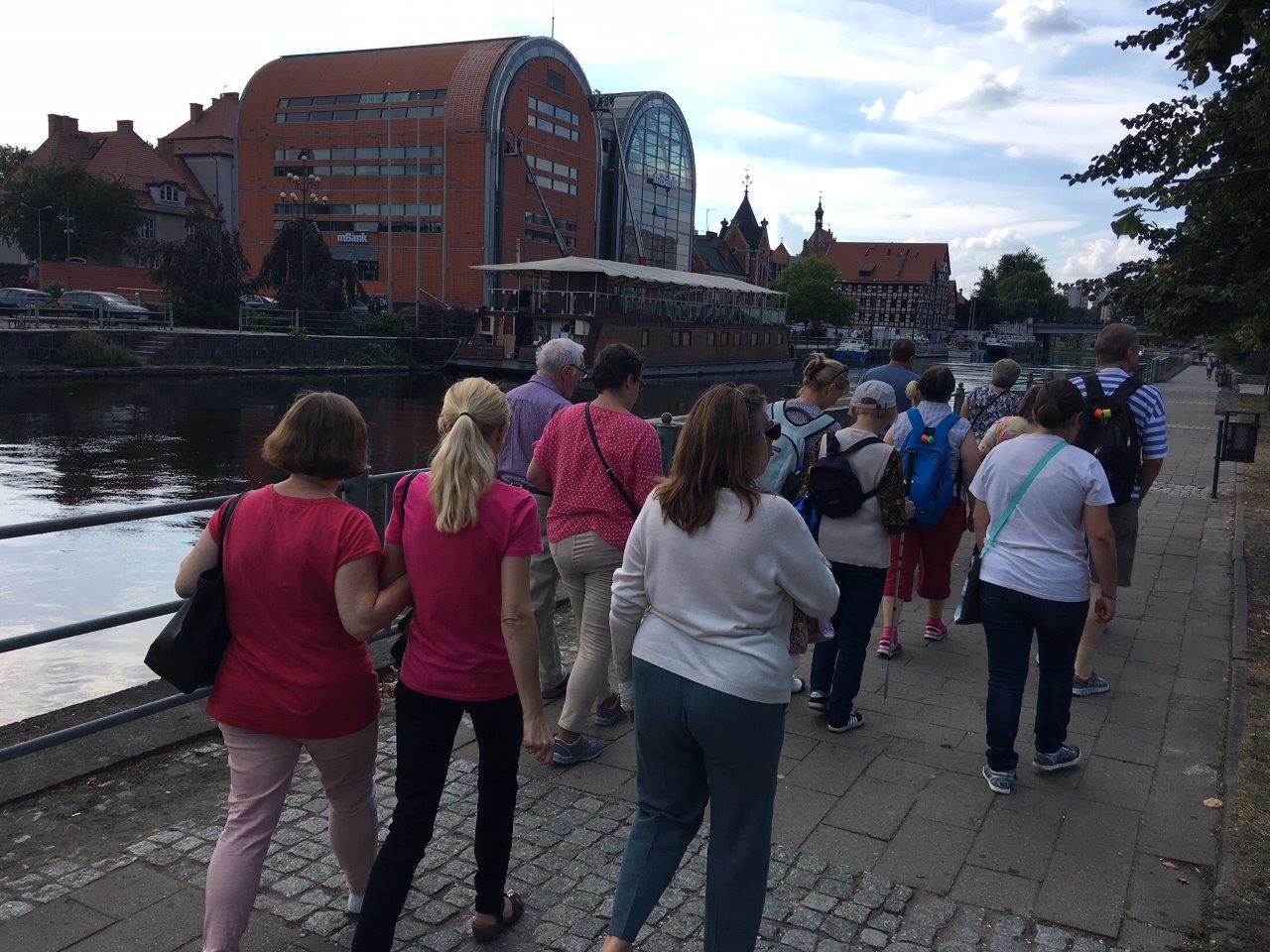 Uczestnicy spacerujący bulwarem, po drugiej stronie Brdy widoczna zabytkowa zabudowa