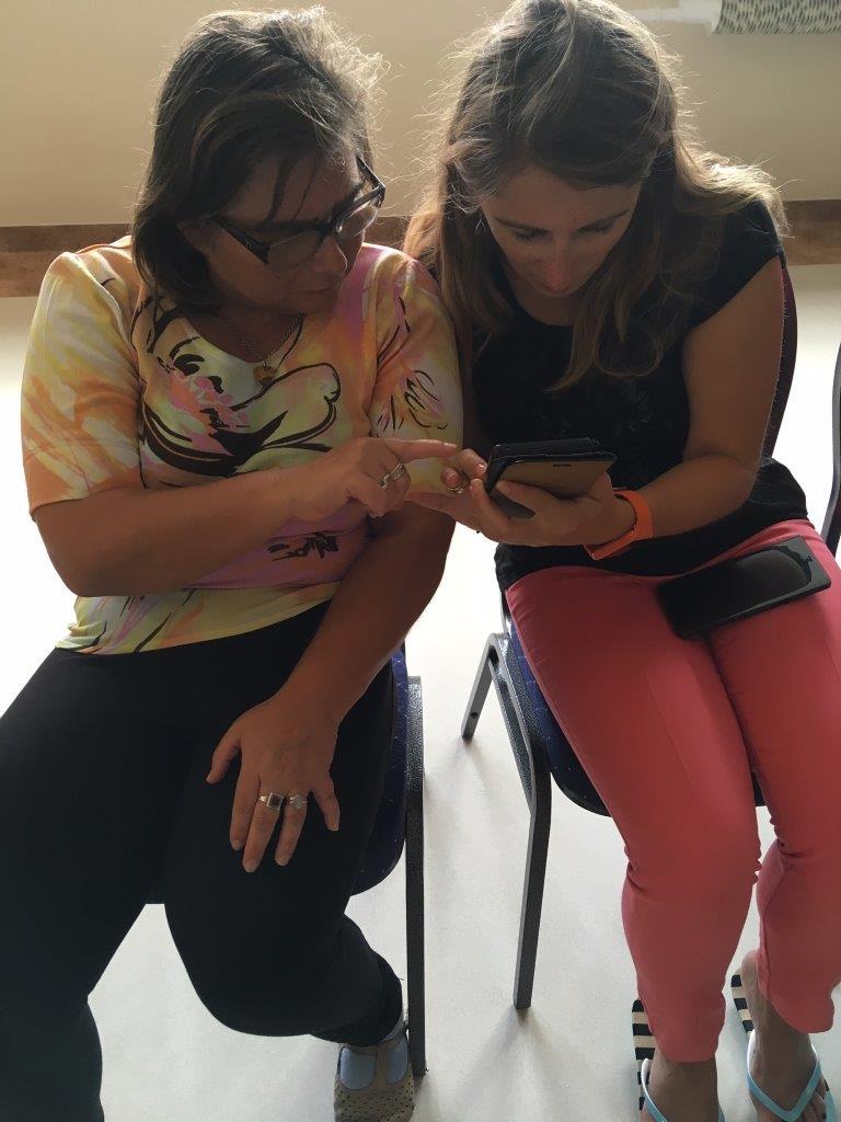 Kursantka i trenerka podczas konsultacji indywidualnych z obsługi smartfonów siedzące obok siebie na krzesłach