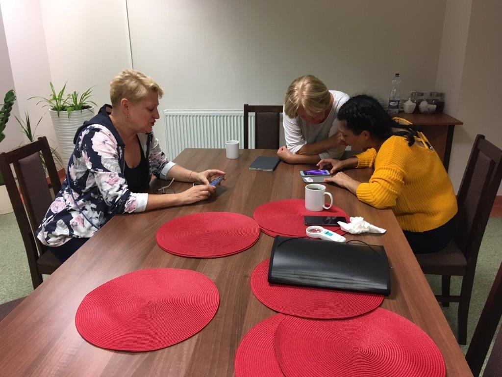 Dwie uczestniczki zjazdu podczas zajęć z obsługi IPhonów siedzące przy brązowym stole z dużymi czerwonymi, okrągłymi podkładkami stołowymi