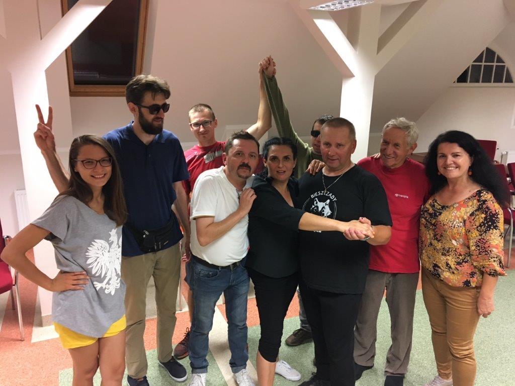 Uśmiechnięta gromadka 9 uczestników [podczas zdjęcia grupowego z wyraźną przewagą męskiej reprezentacji-5 panów