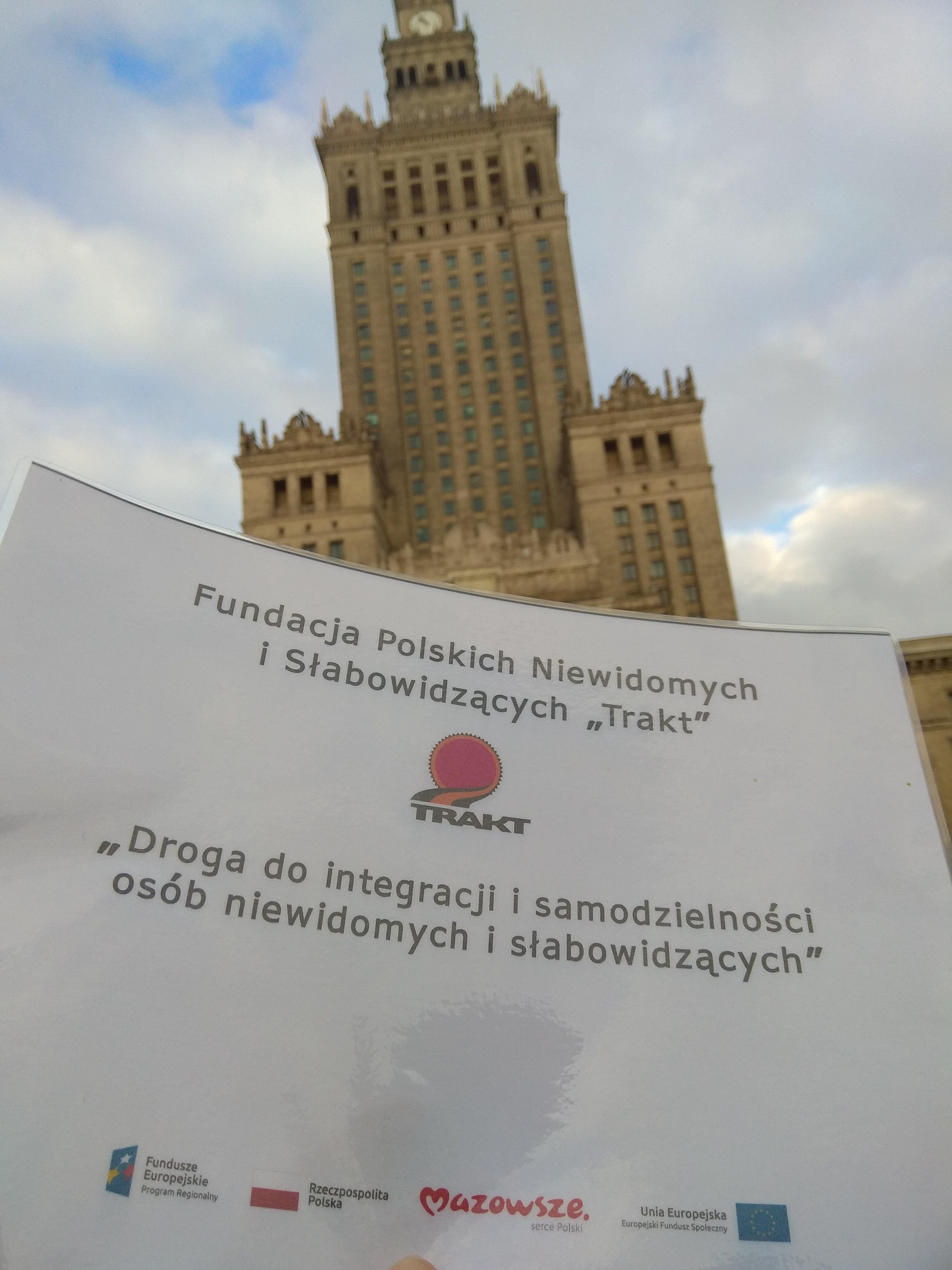 Pałac Kultury i Nauki w Warszawie – wysoki, strzelisty budynek w jasnej kolorystyce z wieloma oknami , a pod nim wkomponowany plakat projektu unijnego.
