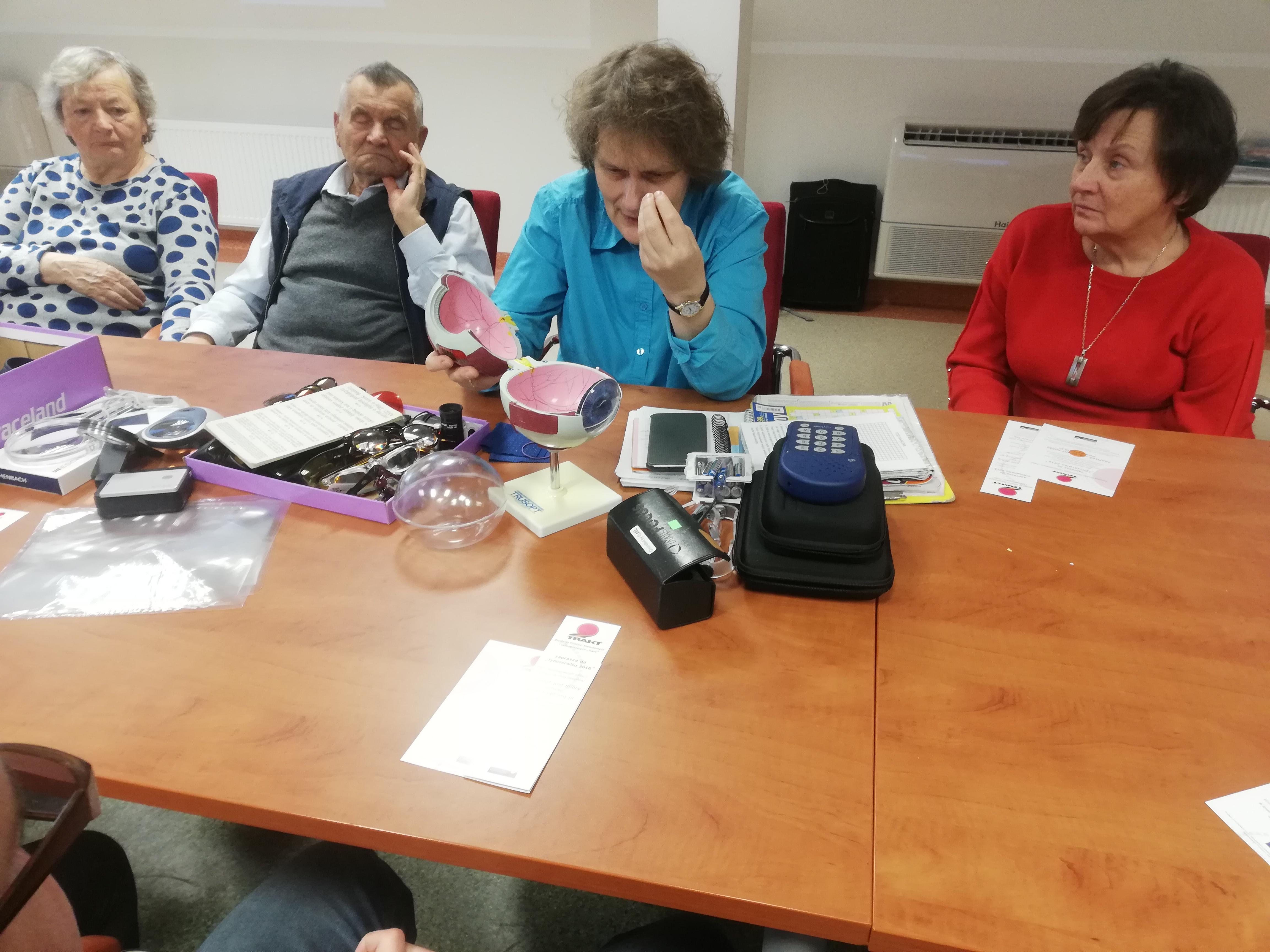 Czterech uczestników zjazdu podczas prezentacji modelu oka siedzący przy prostokątnym stole, wśród nich ubrana w niebieską bluzkę kobieta podczas budowania modelu oka, na stole widoczne jego różne elementy.