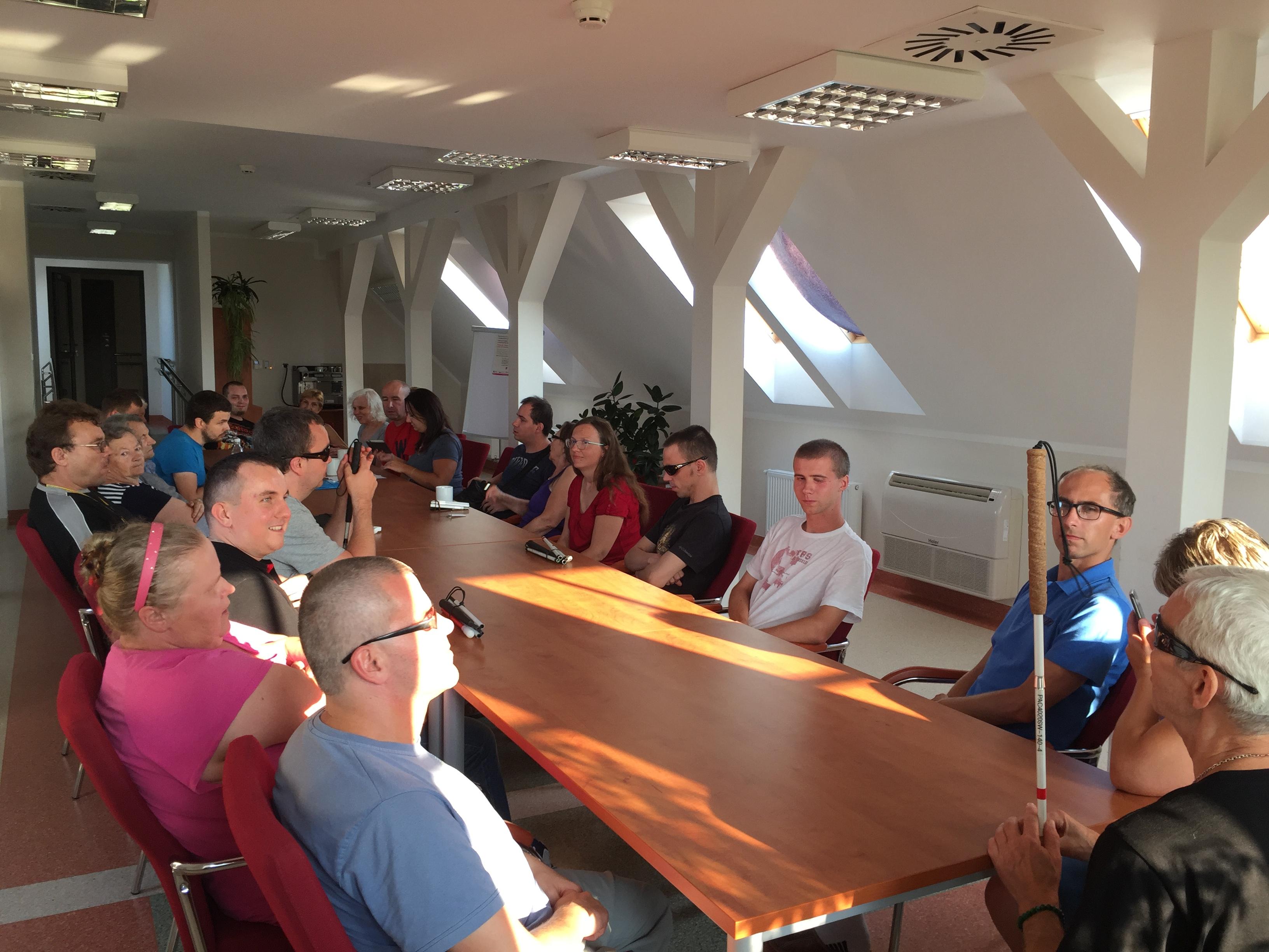Grupa uczestników zjazdu siedząca przy długim stole w Sali konferencyjnej podczas szkolenia