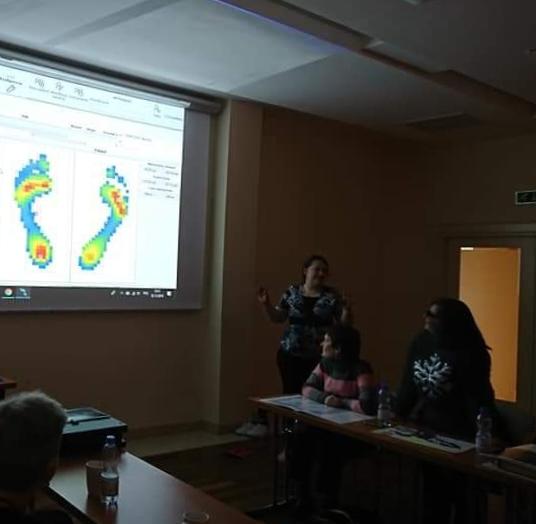 Uczestnicy zebrani w sali konferencyjnej w przyciemnionym świetle, widoczny duży ekran ścienny, a na nim prezentacja wyniku badania komputerowego stóp, wielobarwny obraz  ich podeszwowej części.