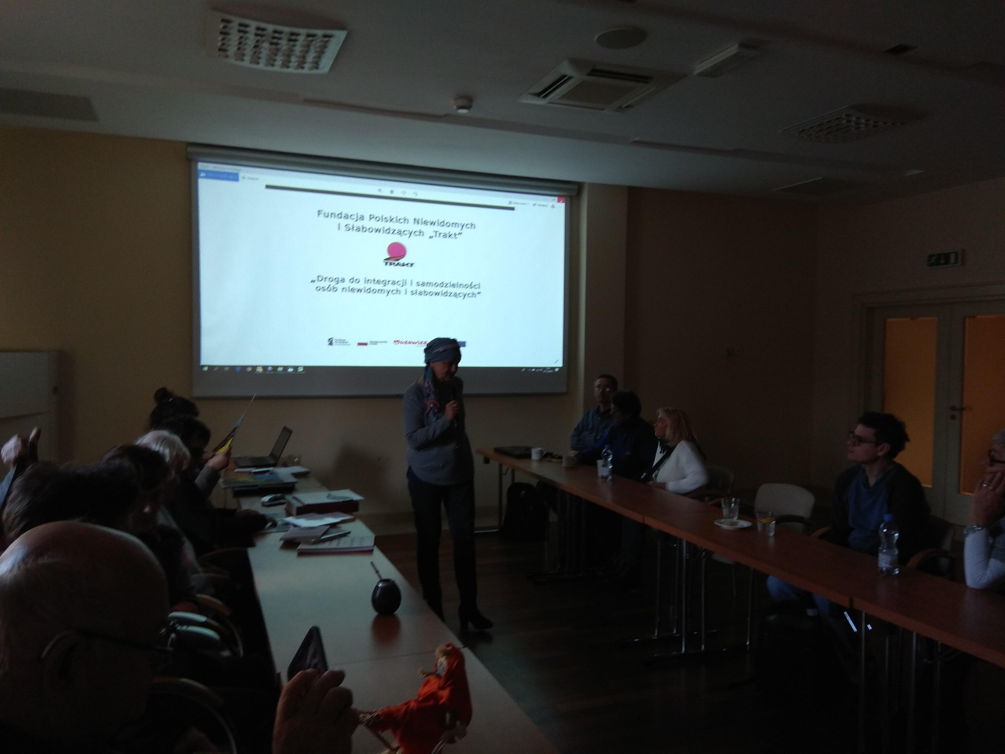Uczestnicy siedzący w sali konferencyjnej ze stołami ustawionymi po bokach wzdłuż sali podczas szkolenia, na przedniej ścianie widoczny duży ekran z logo Fundacji TRAKT i jej pełną nazwą oraz tytułem projektu unijnego.