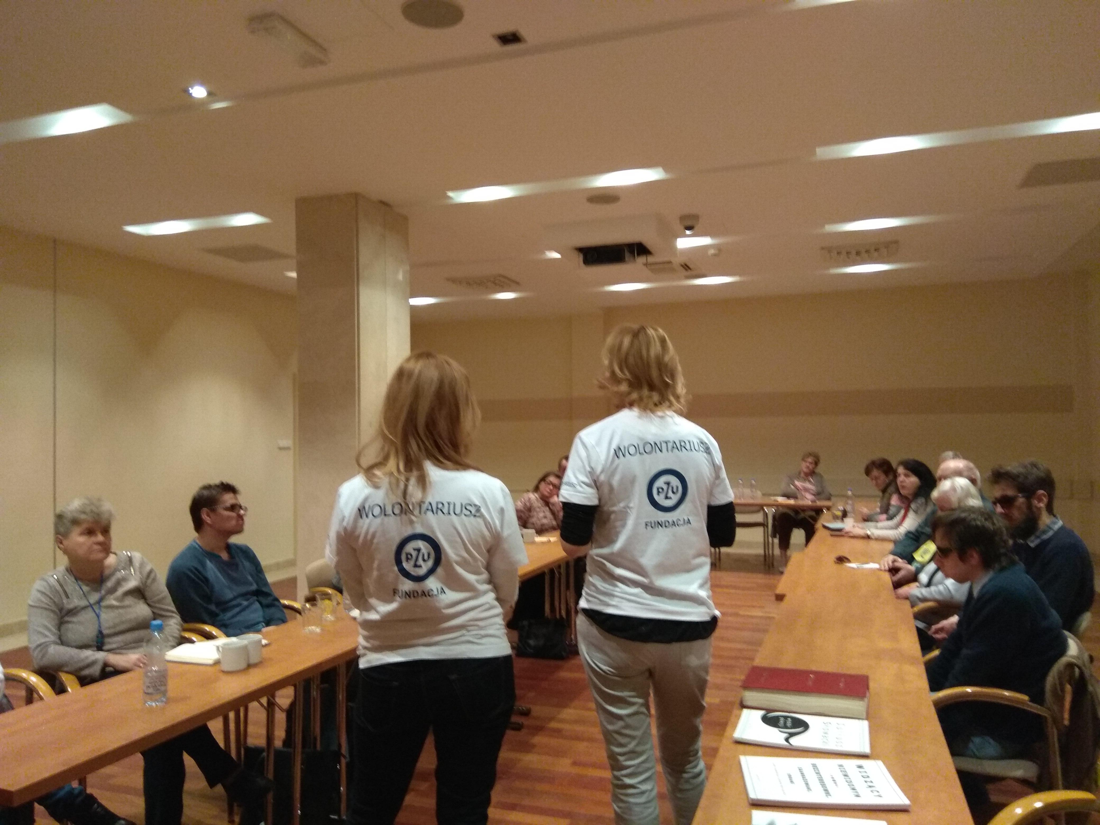 W jasnej przestrzeni sali konferencyjnej widoczni uczestnicy zjazdu siedzący po bokach sali, a w środku między stołami stojące dwie panie, obie blondynki,  w białych koszulkach widziane od tyłu, na koszulkach logo Fundacji PZU, jej nazwa i napis Wolontariusz.