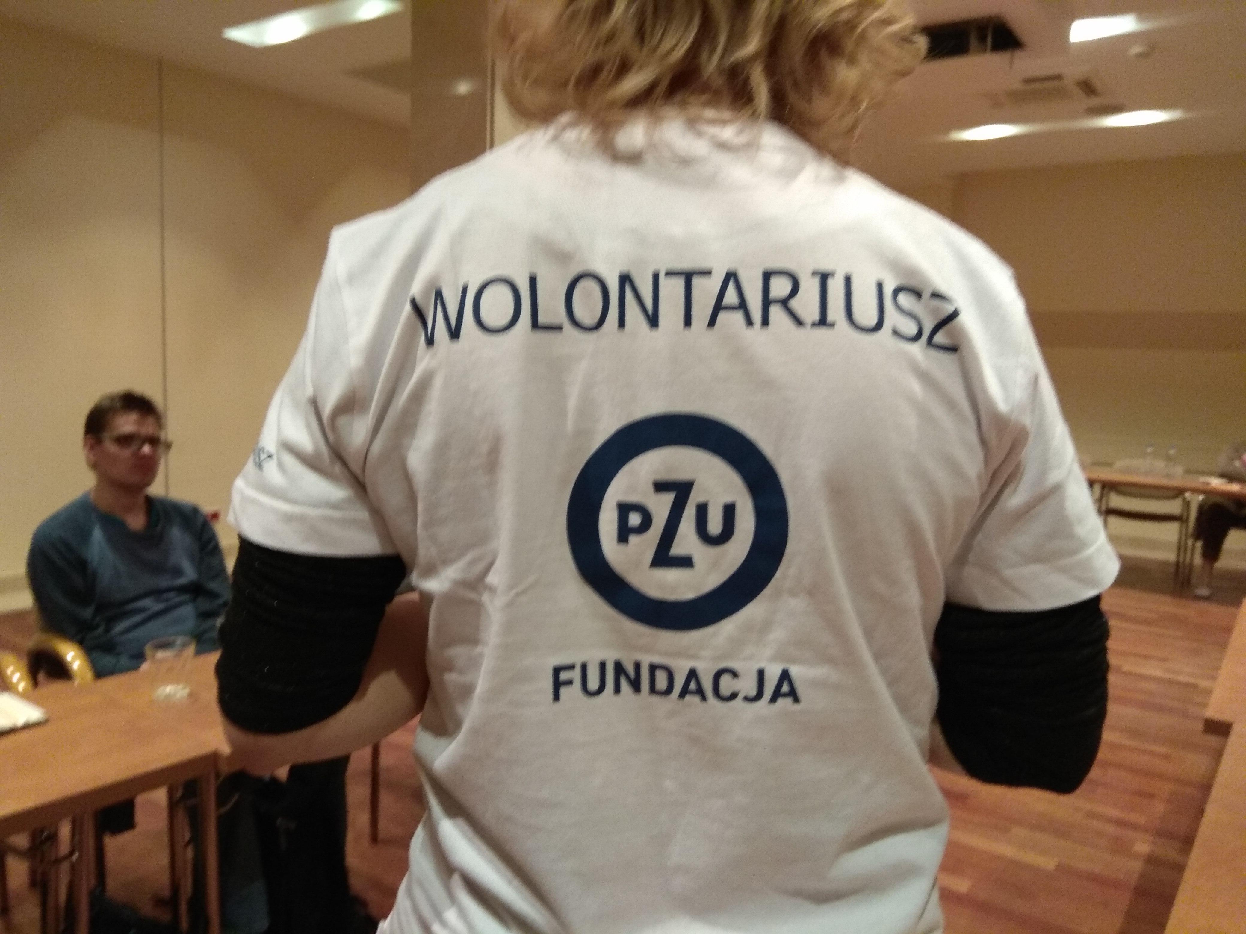 W zbliżeniu widziana od tyłu pani w białej koszulce z krótkim rękawem, pod nim widoczne długie czarne rękawy, na koszulce napis Wolontariusz, pod nim okrągłe logo z napisem w środku PZU, a pod logo hasło Fundacja  PZU.