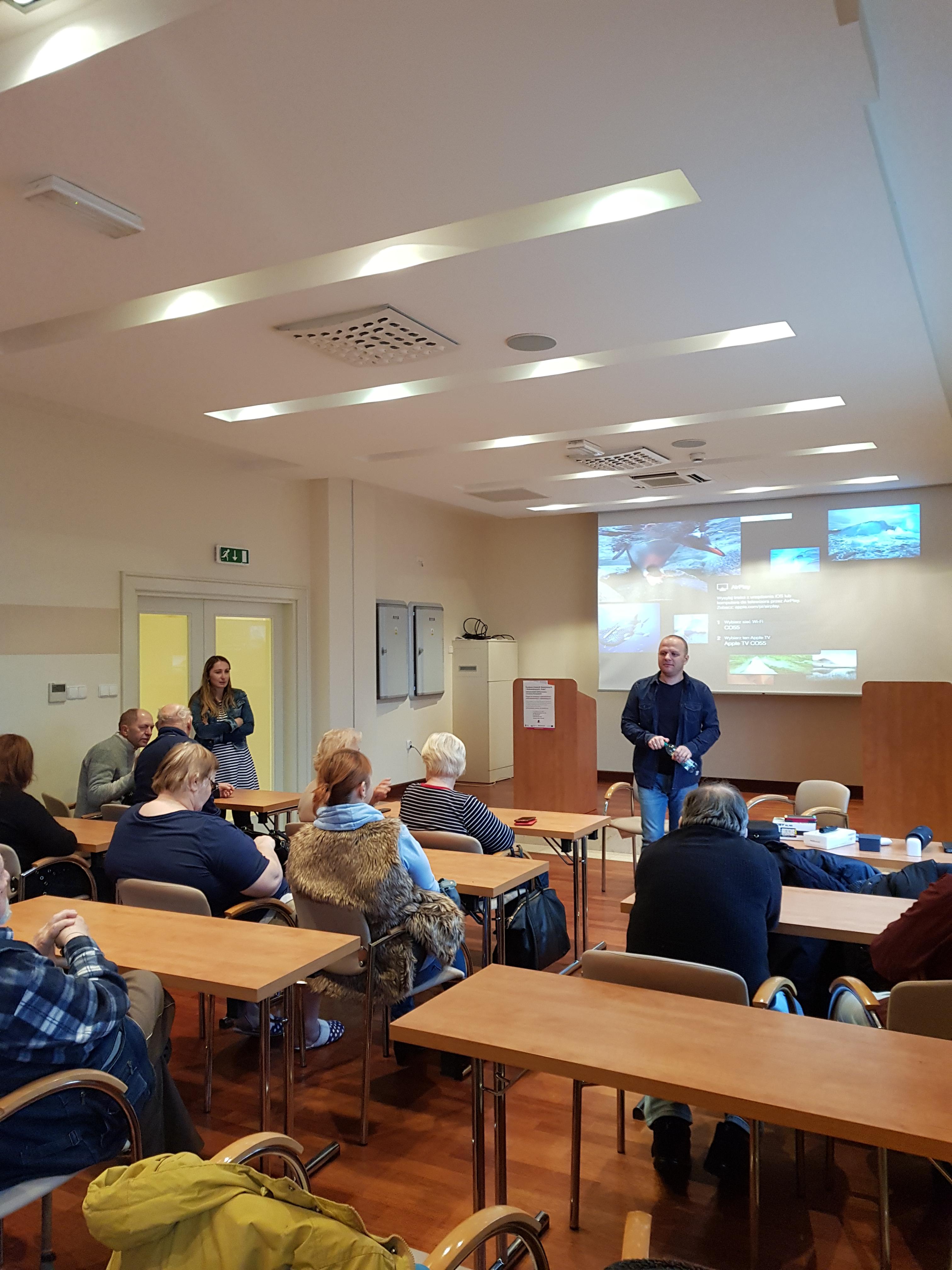 Uczestnicy zjazdu podczas pierwszego dnia zajęć z obsługi smartfonów zgromadzeni w sali konferencyjnej z układem stołów jak w sali szkolnej, z przodu para mieszana szkoleniowców podczas prezentacji, w tle widoczny duży wyświetlacz ścienny