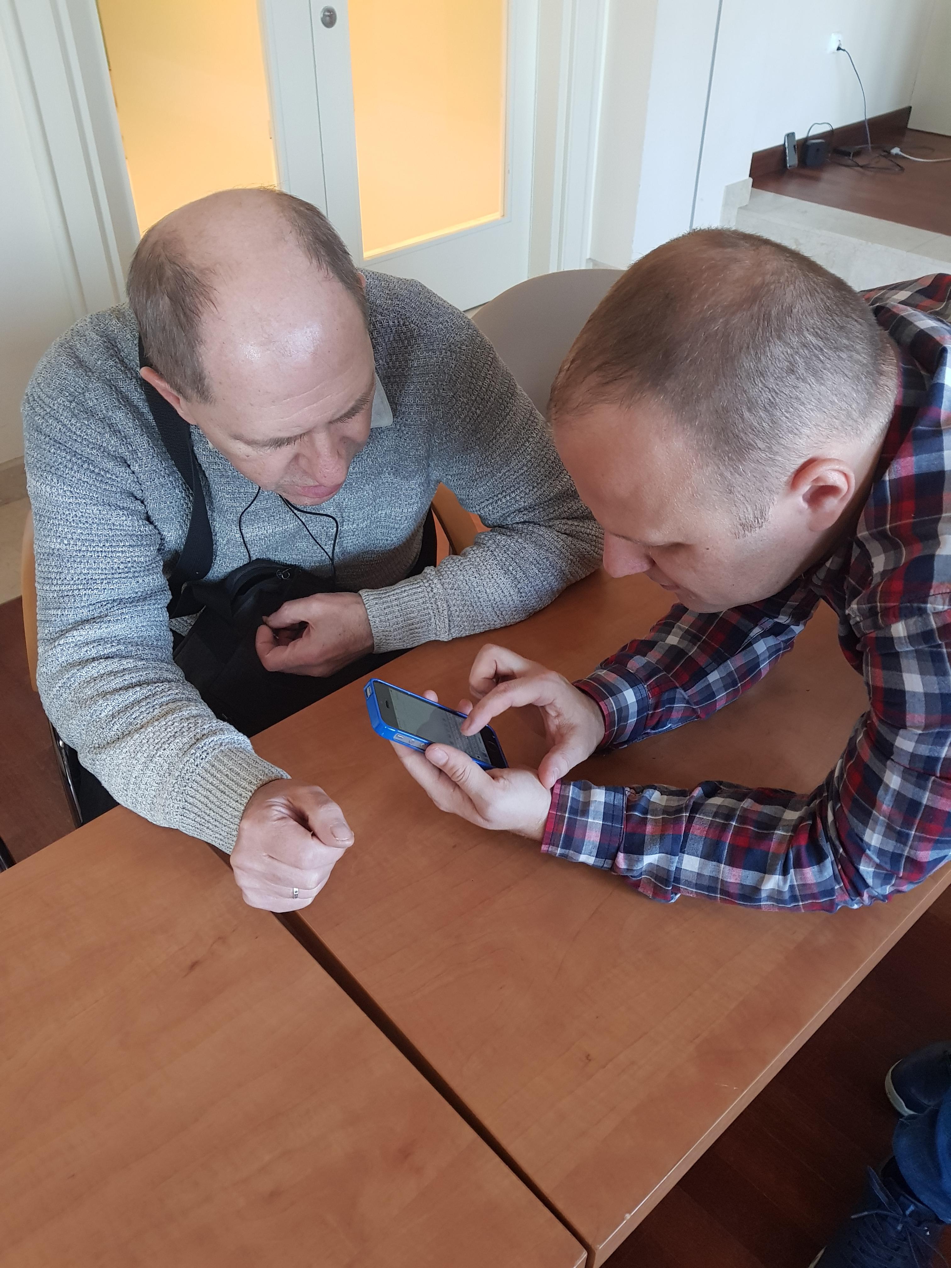 Trener podczas konfigurowania iPhone'a jednego z panów, z lewej siedzący uczestnik ubrany w szary sweter, przy nim instruktor w koszuli w kratę biało-czarno-czerwoną trzymający w ręku iPhone