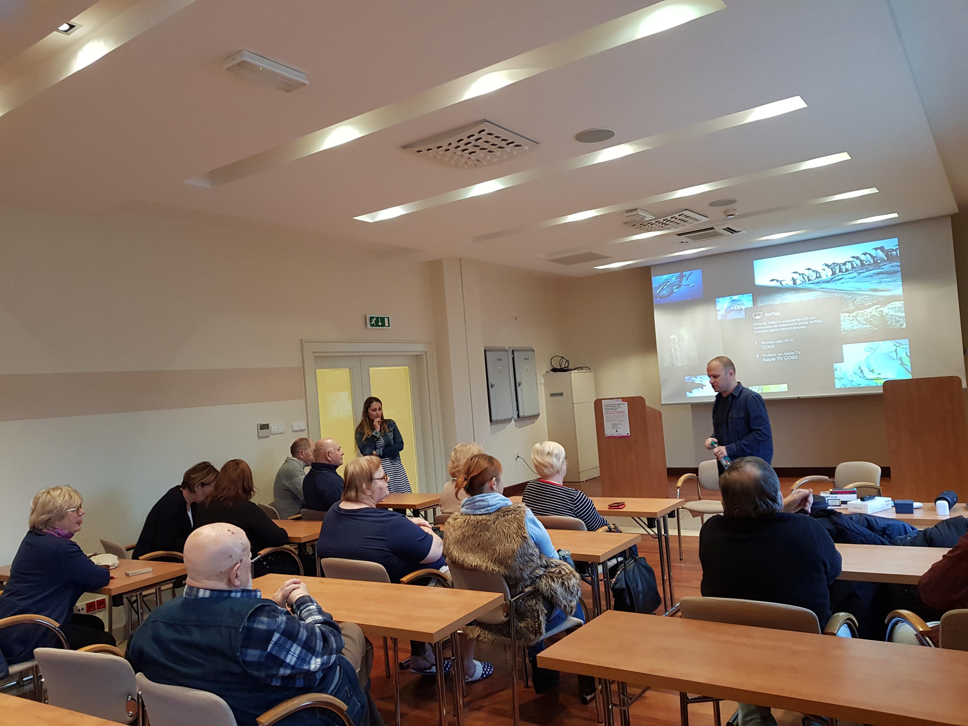 Kolejna godzina szkolenia, uczestnicy zgromadzeni w sali konferencyjnej podczas prezentacji, po lewej przy drzwiach widoczna stojąca trenerka, a na tle ekranu ściennego stoi instruktor